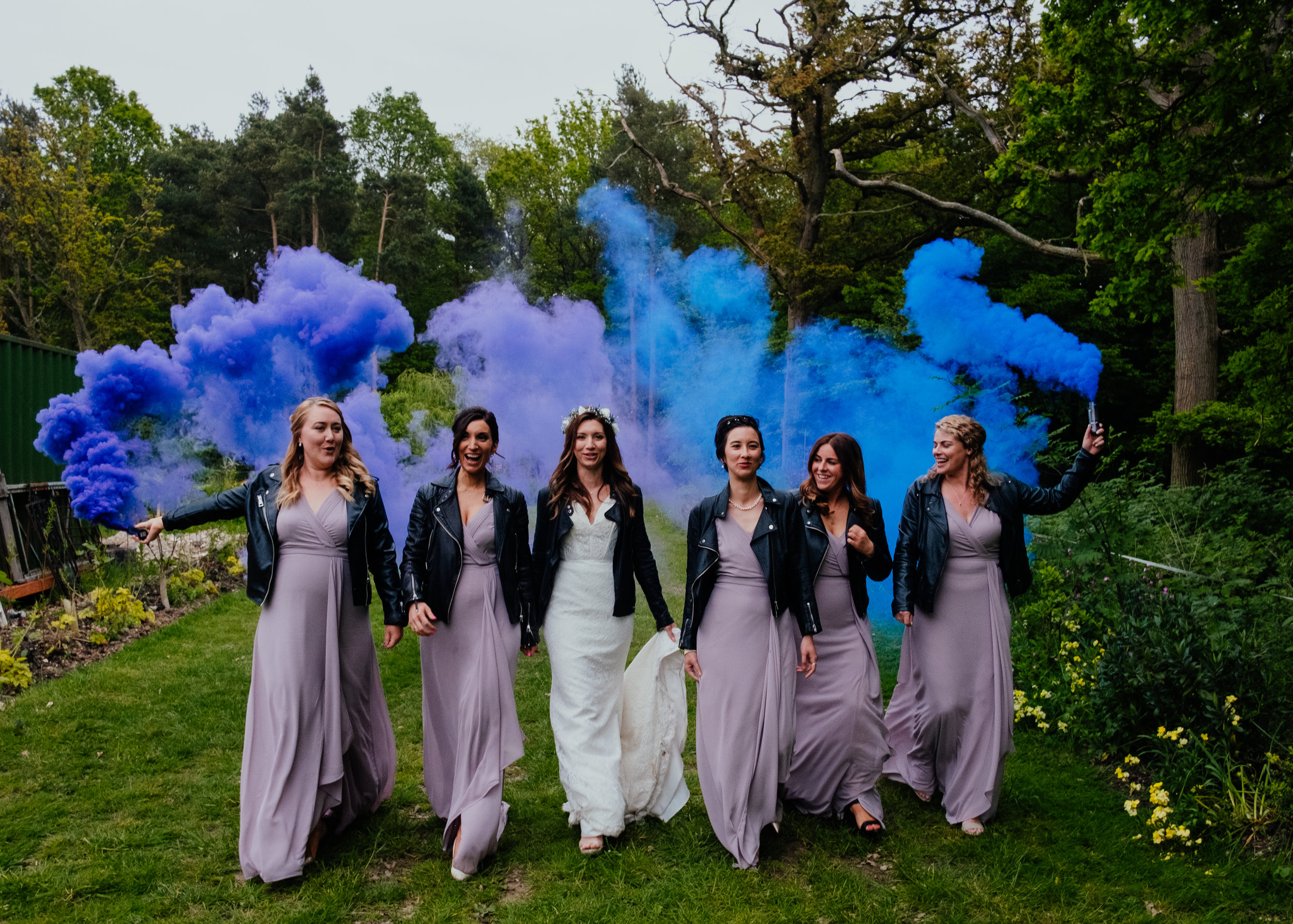 Badass bridesmaids walking along with the bride holding coloured smoke grenades