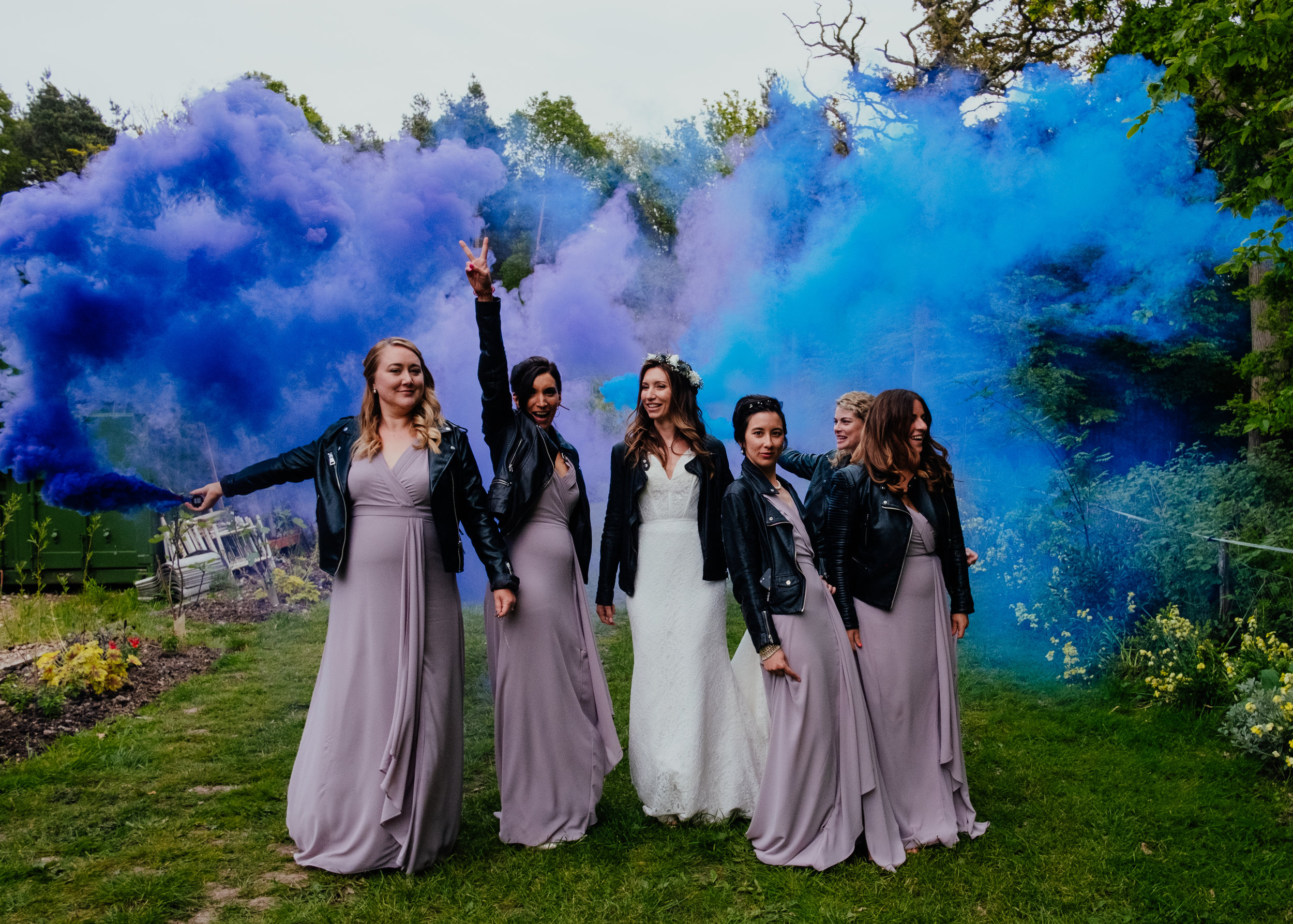 Bride and Bridesmaids stood with coloured smoke grenades | Captains Wood Barn wedding photography