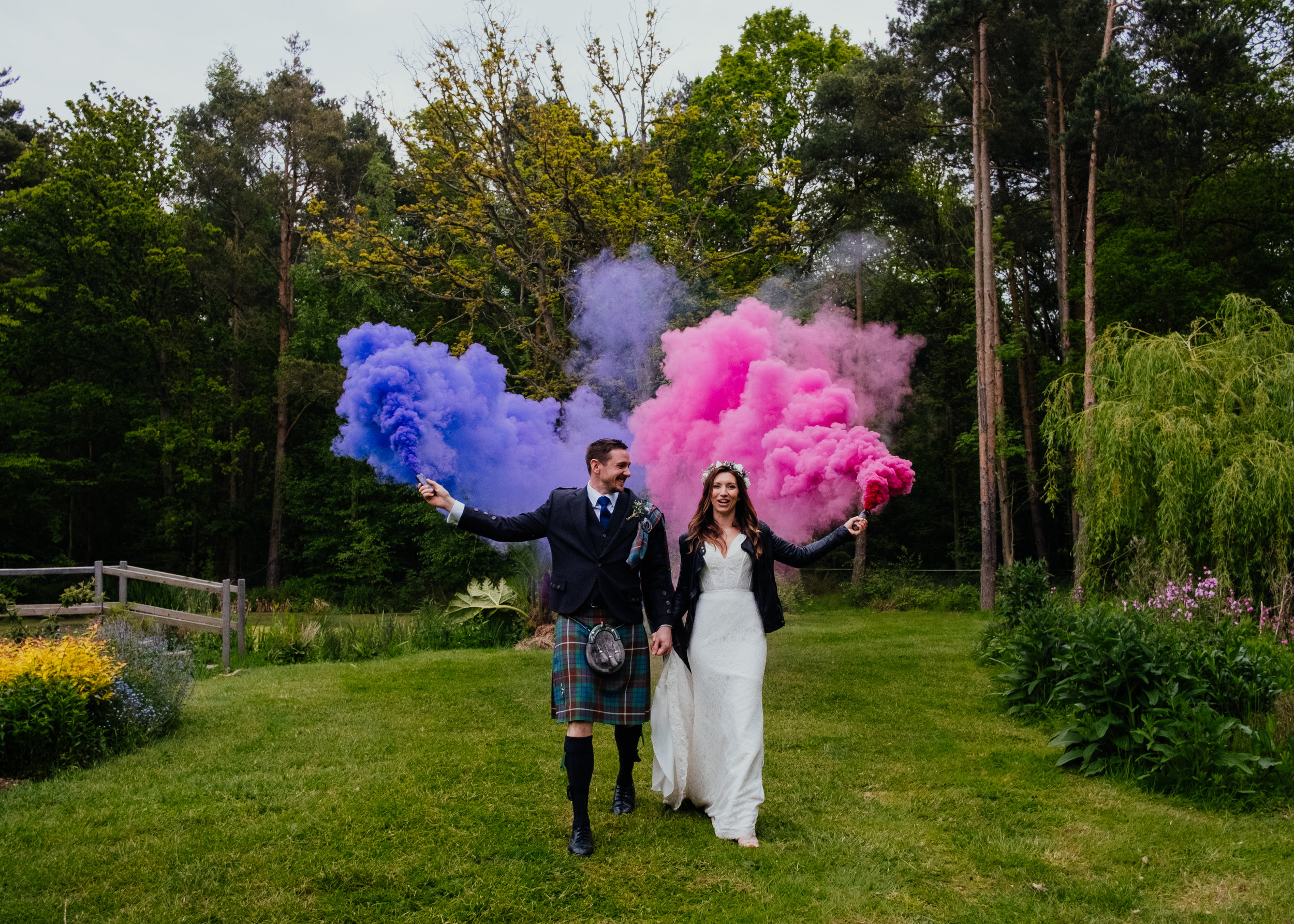 Bride and groom walking along with coloured smoke grenades