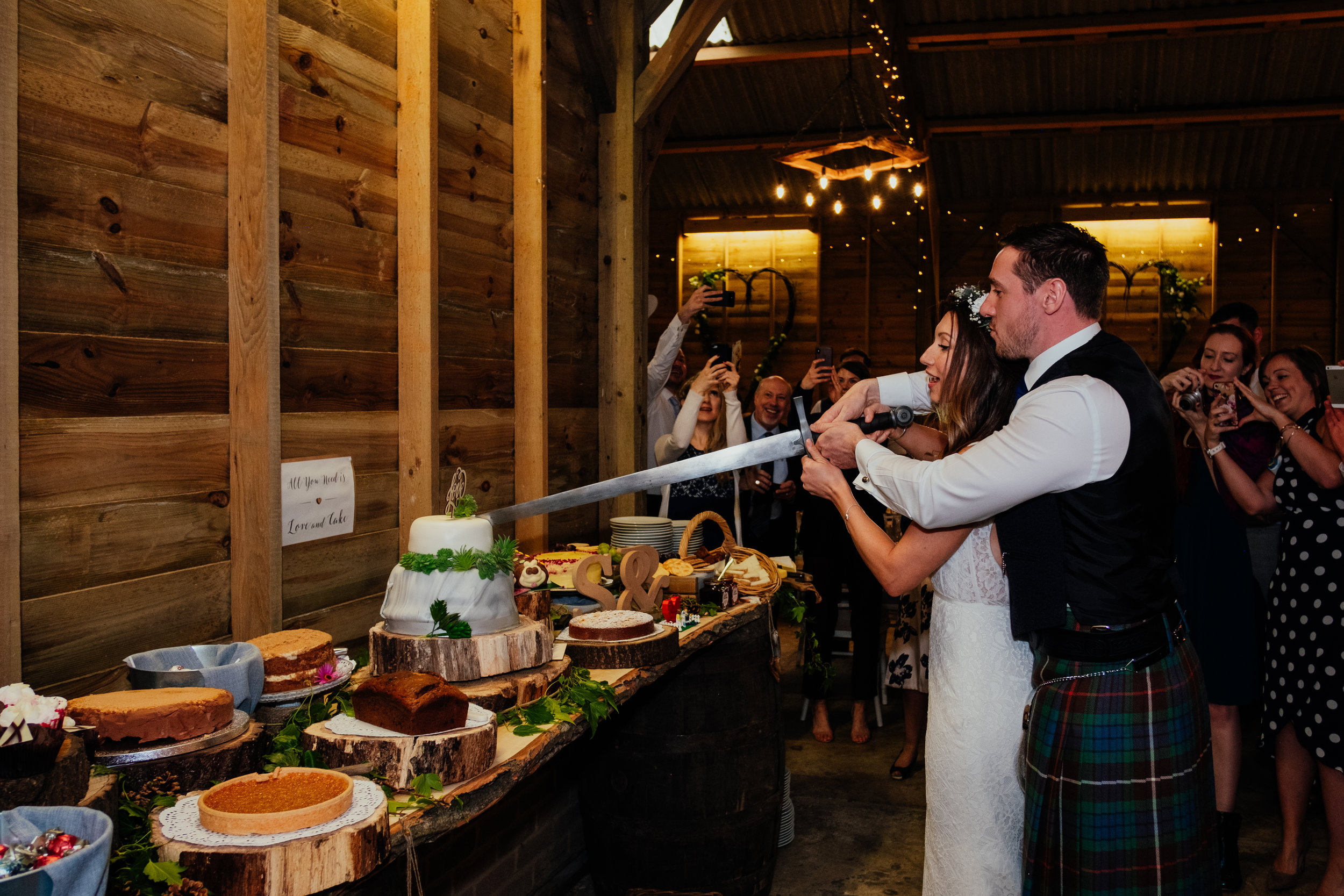 Bride and groom cut the cake at Captains Wood Barn wedding