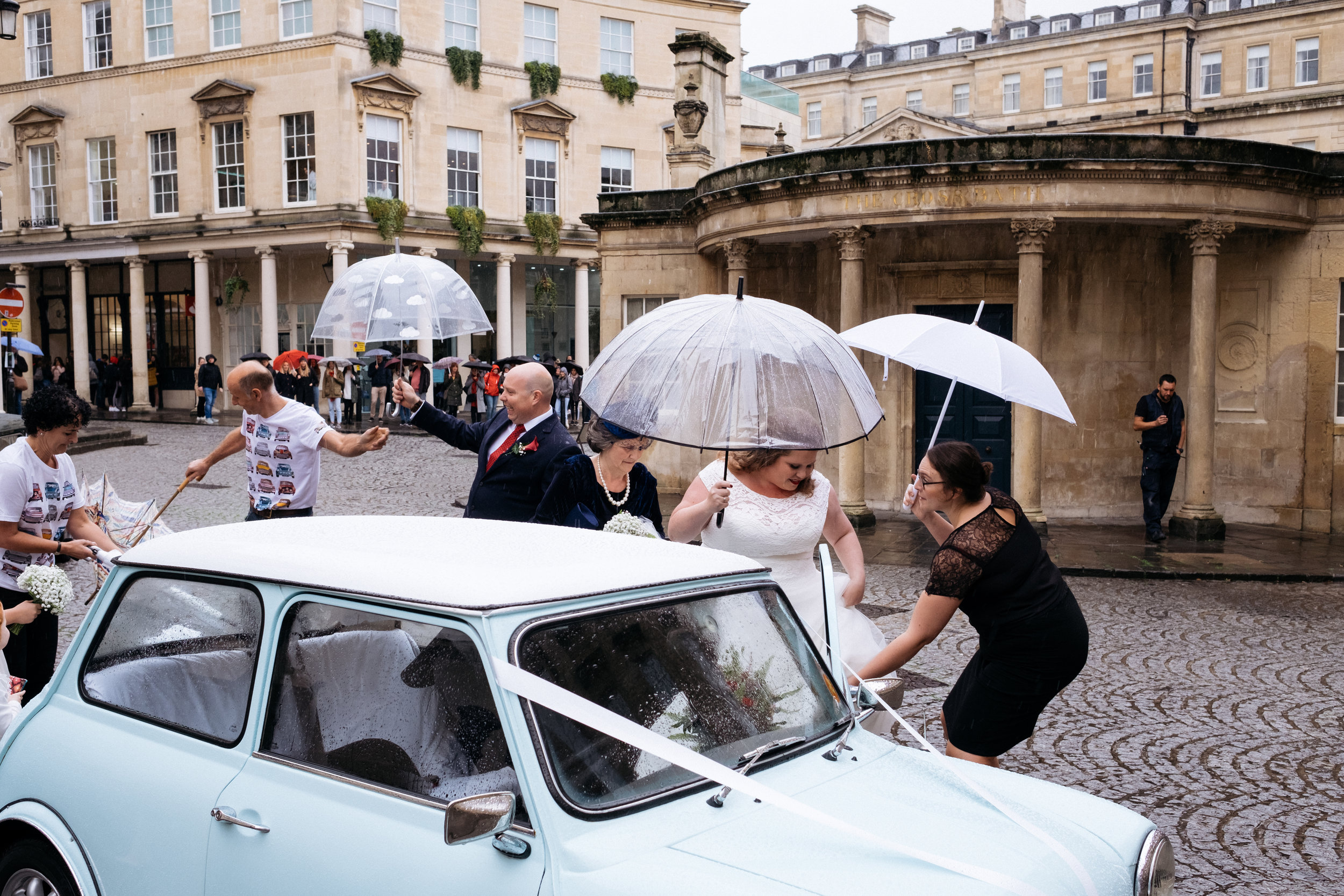 Bride getting out of classic mini wedding car at the Little Theatre in Bath