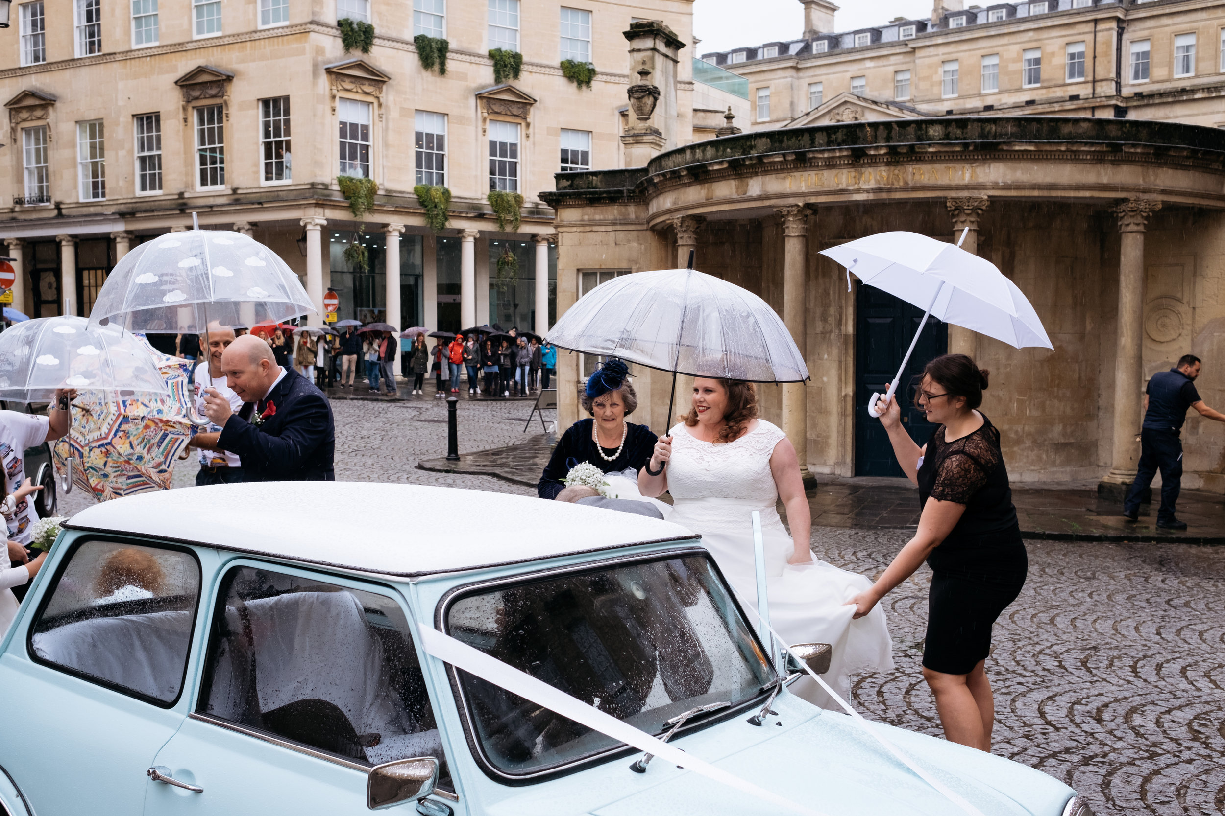 Bride smiles as she gets out of classic mini wedding car at the Little Theatre in Bath