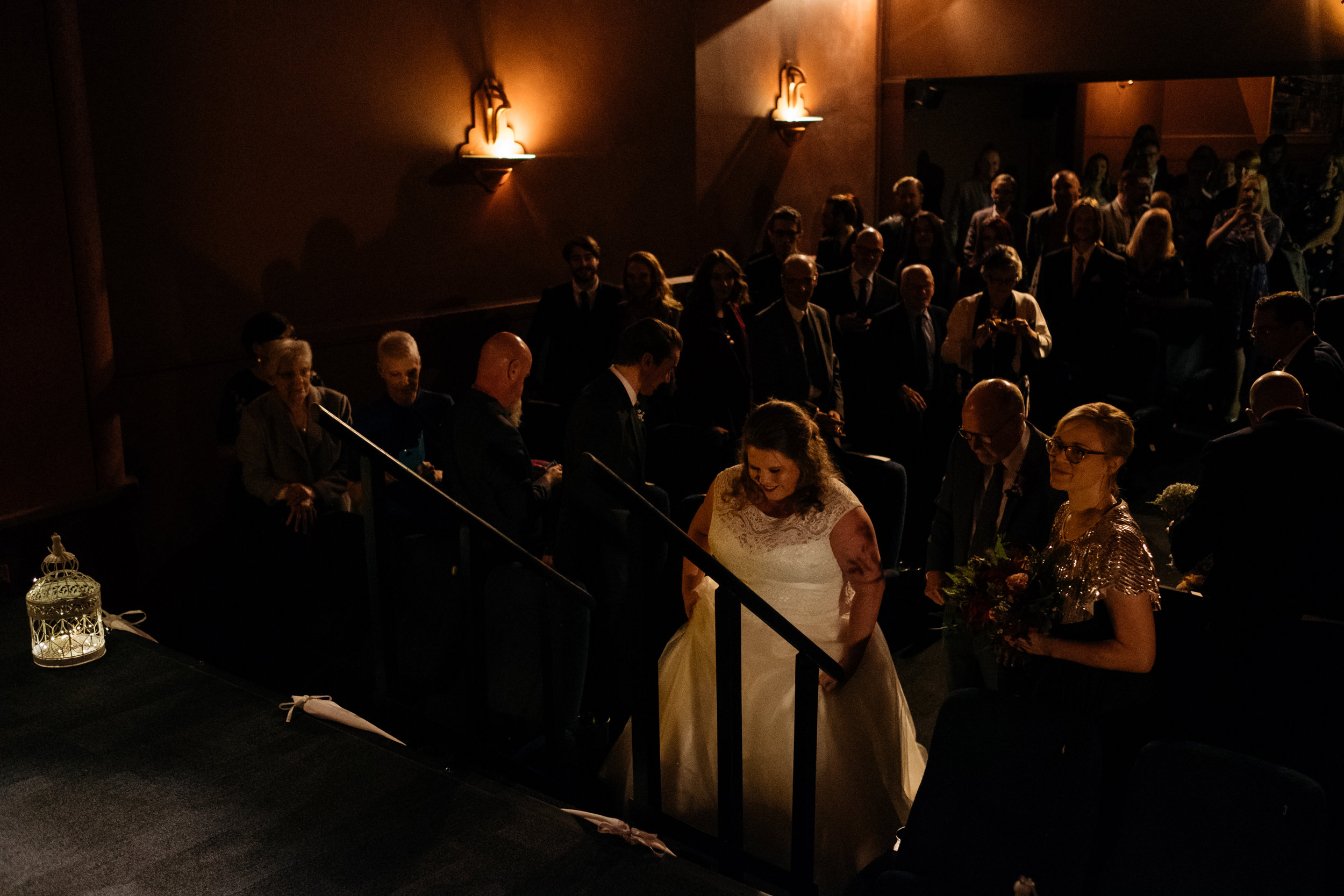 Bride walks along aisle in the Little Theatre in Bath
