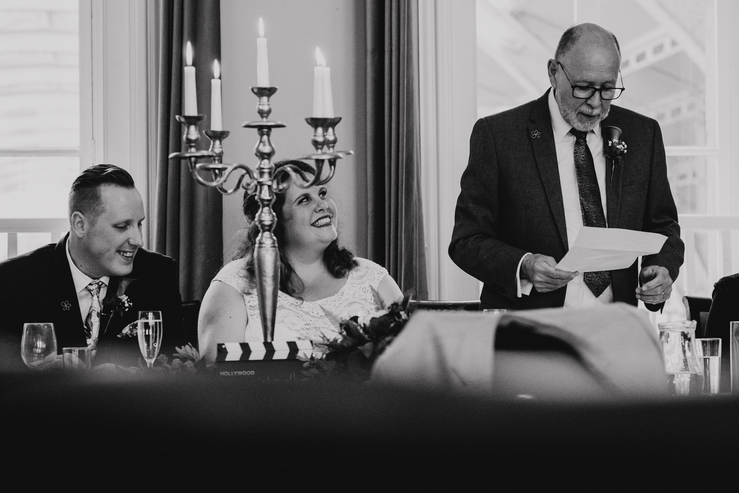 Bride smiles at Father of the Bride as he gives wedding speech