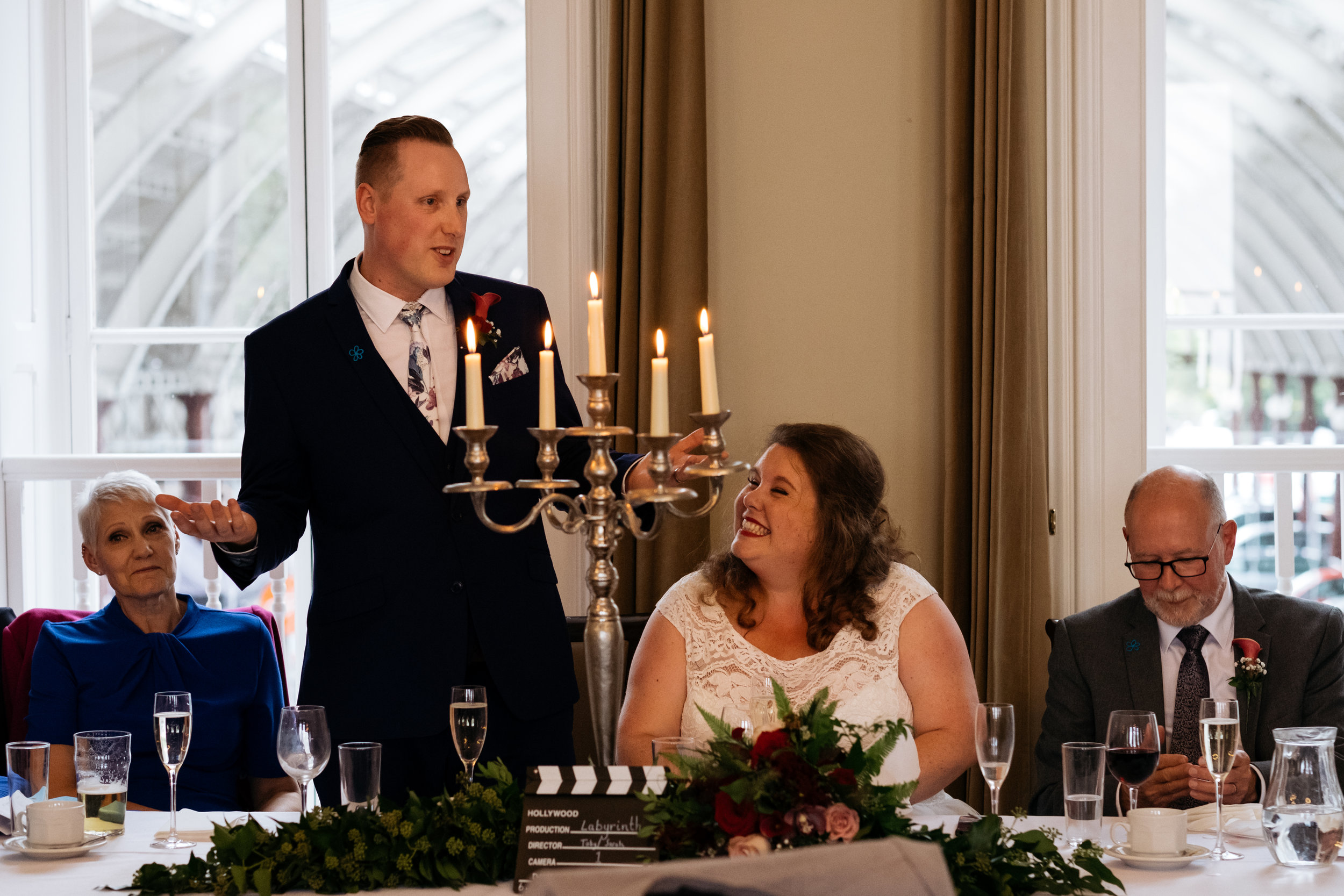 Bride grinning as Groom reads wedding speech