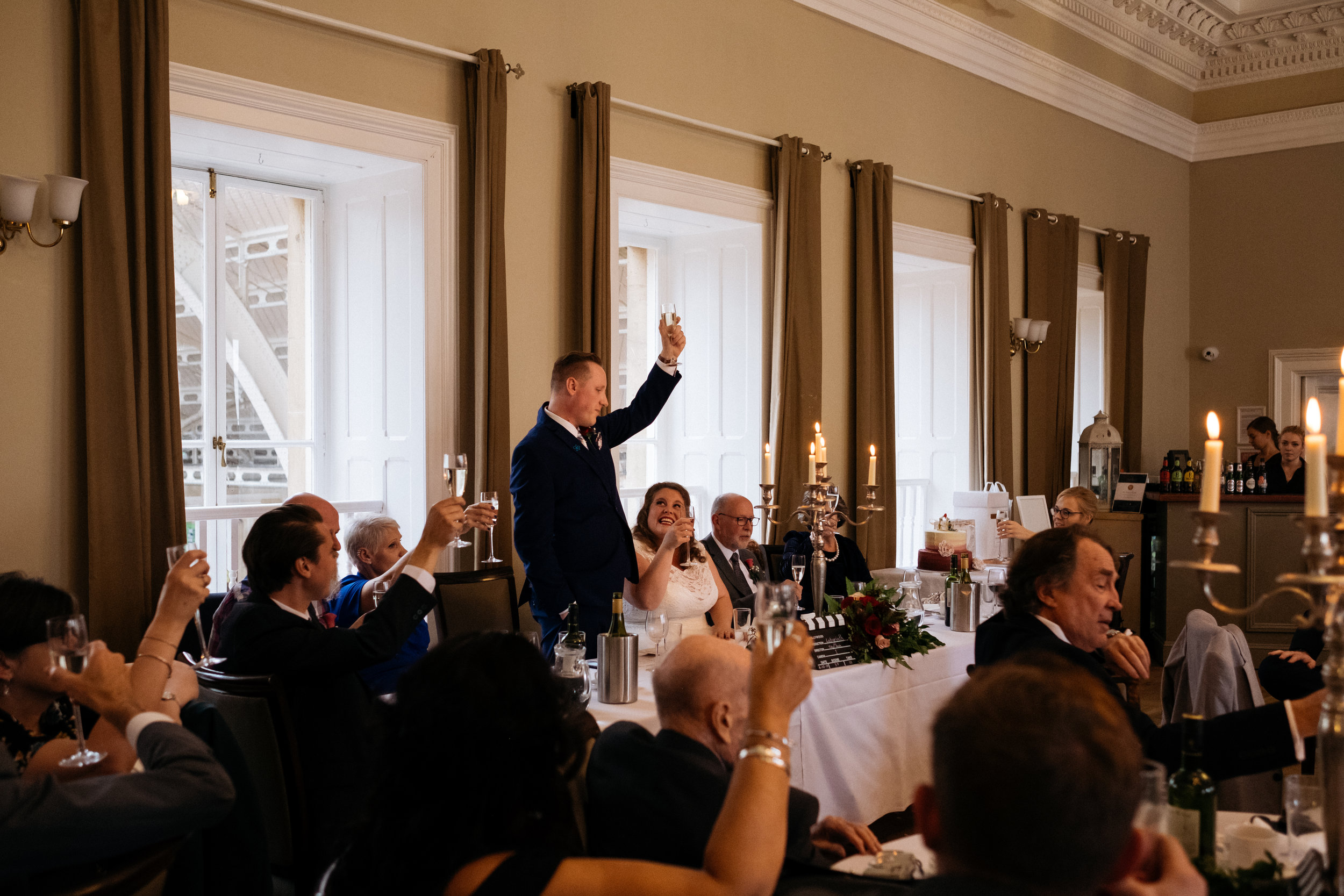 Groom raises glass in toast to all wedding guests