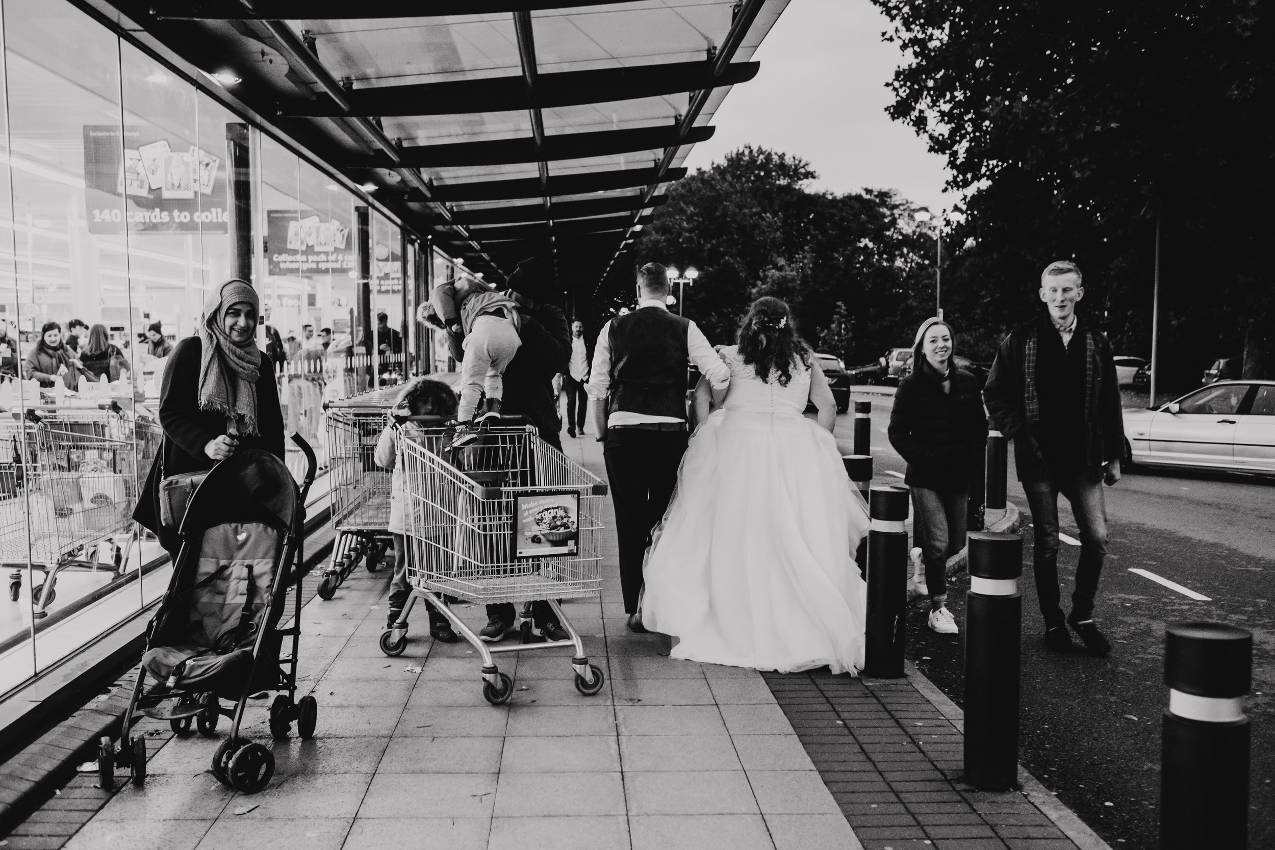 Bride and Groom walk past Sainsburys