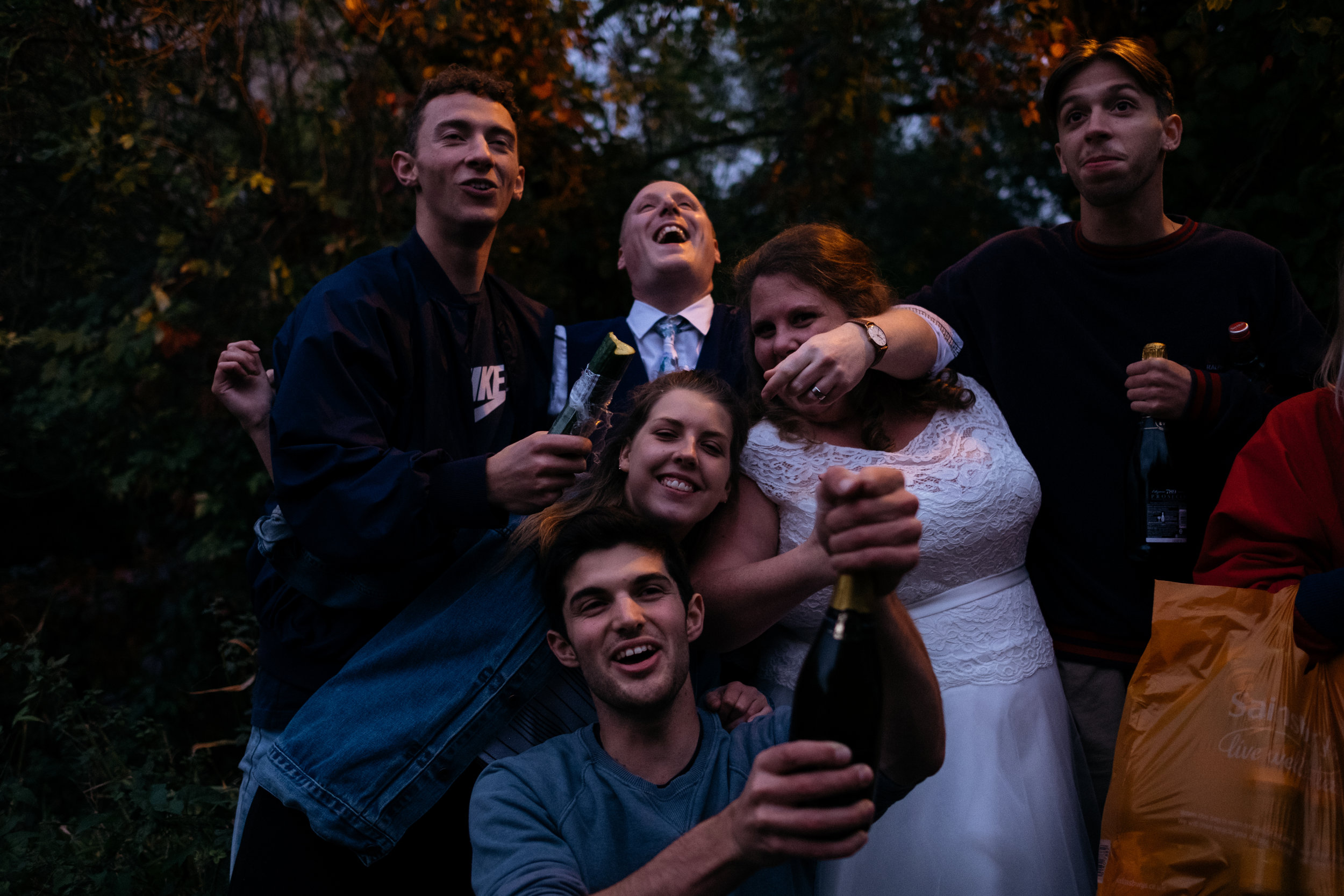 Group of people with bride and groom and bottle of prosecco