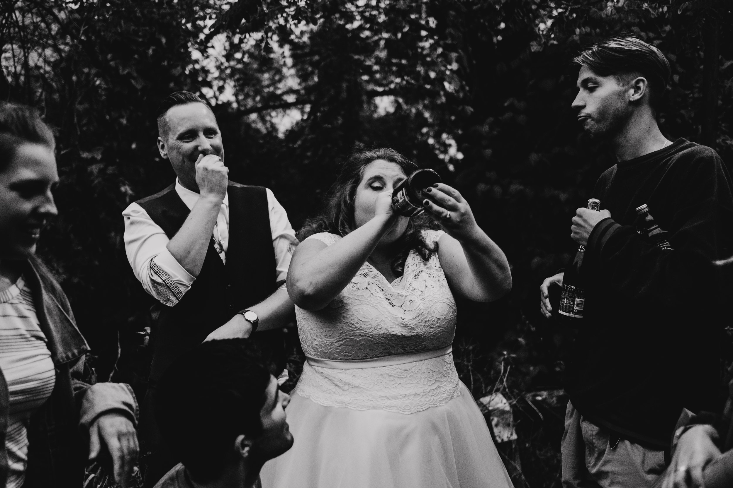Bride drinking champagne from the bottle