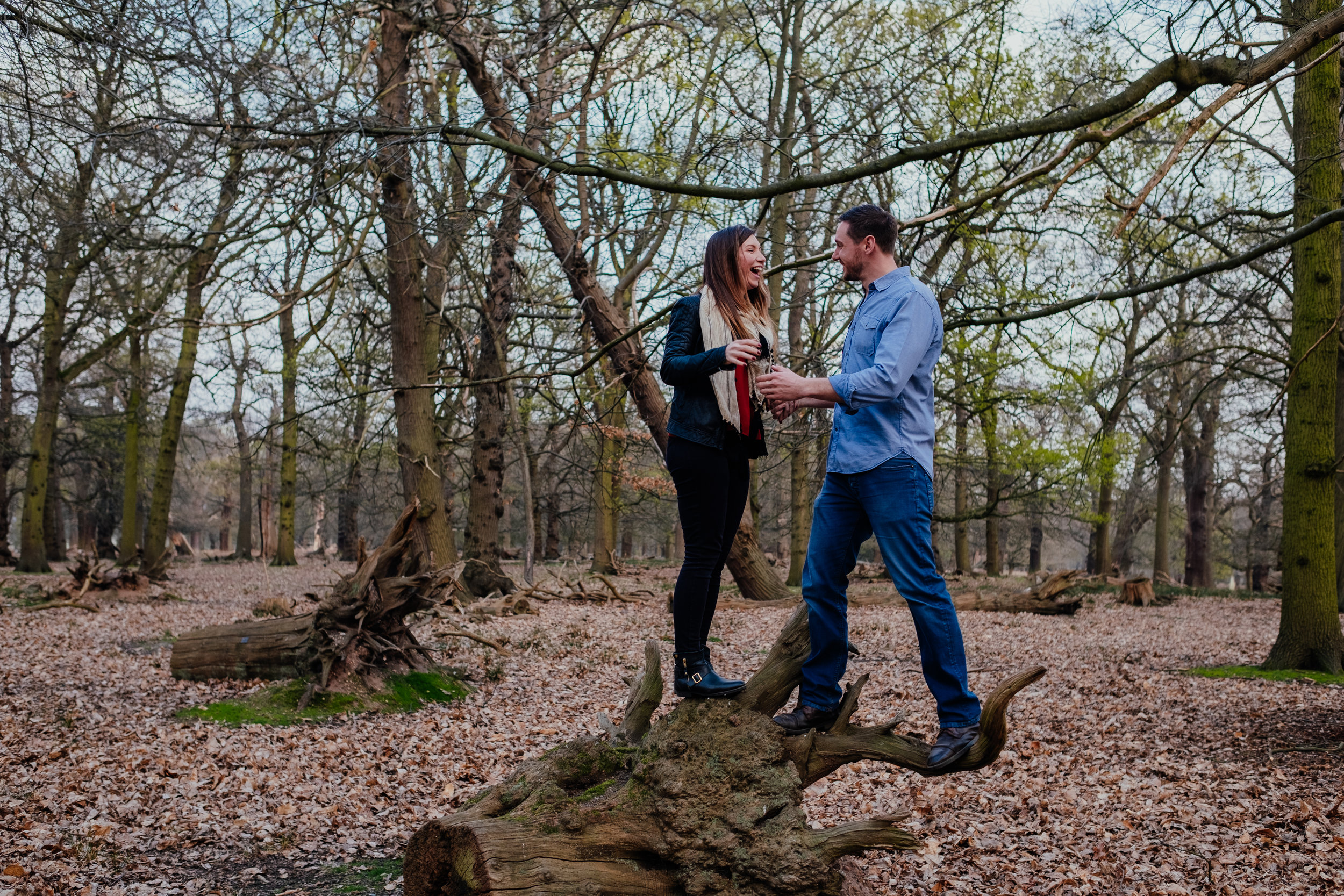 Couple laughing and climbing trees in Richmond Park