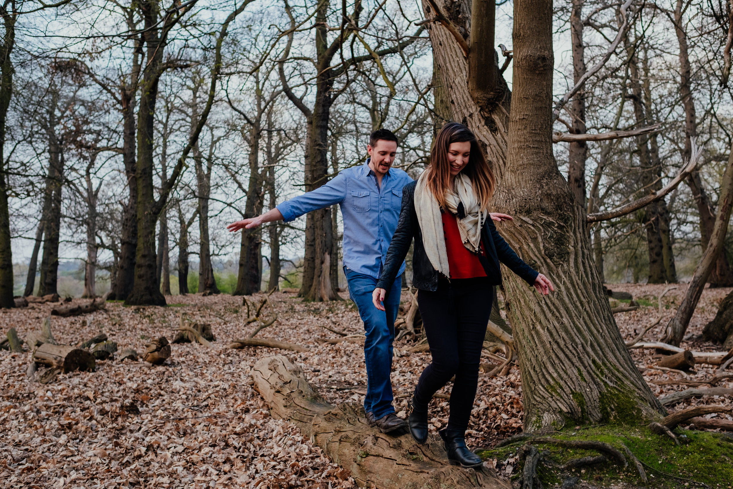 Couple walking along fallen tree in Richmond Park during engagement shoot