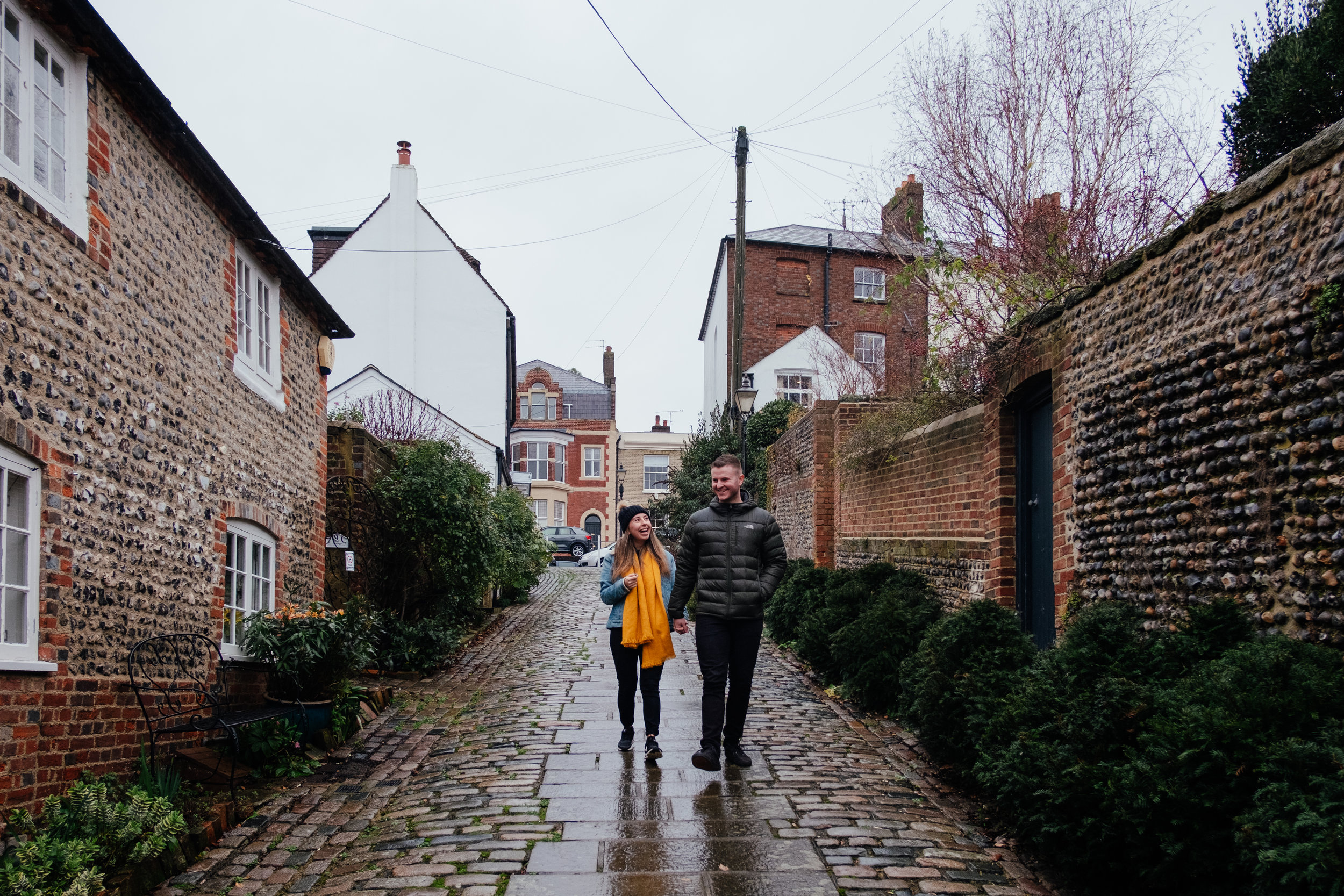 Couple walking down cobbled street in Arundel during engagement shoot