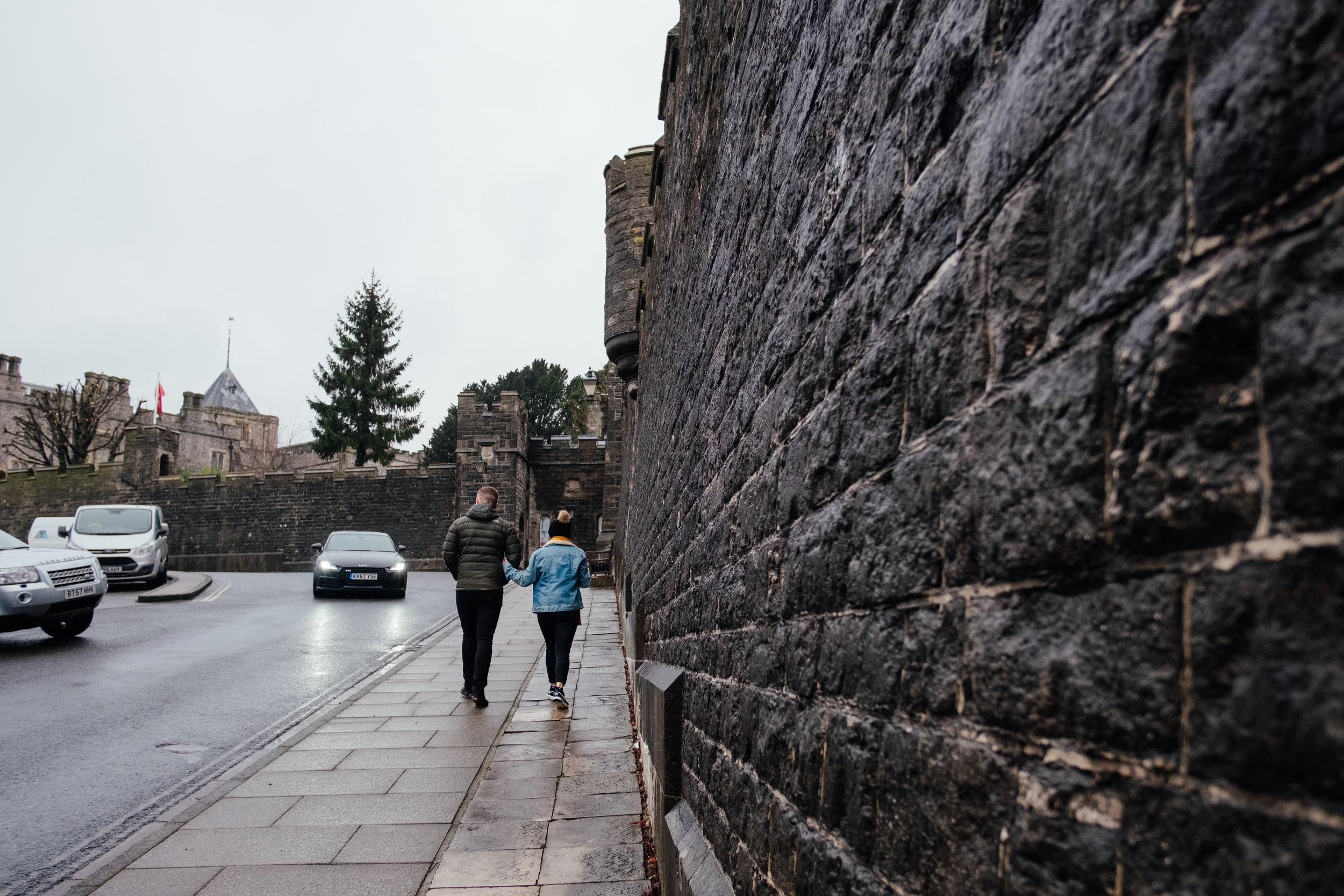 Couple walking alongside Arundel Castle