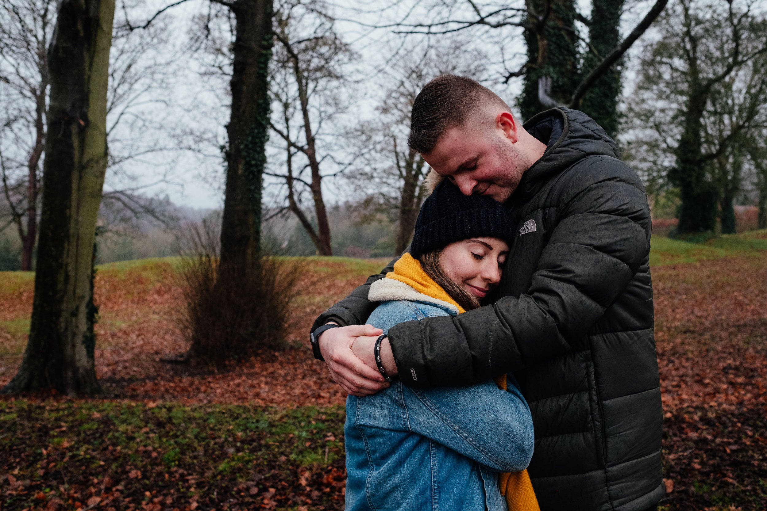 Couple cuddling during winter engagement shoot in Arundel park