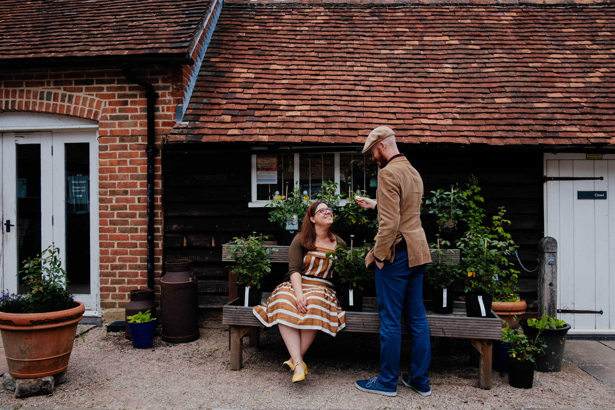 Couple looking at flowers during engagement shoot | Hampshire wedding photographer