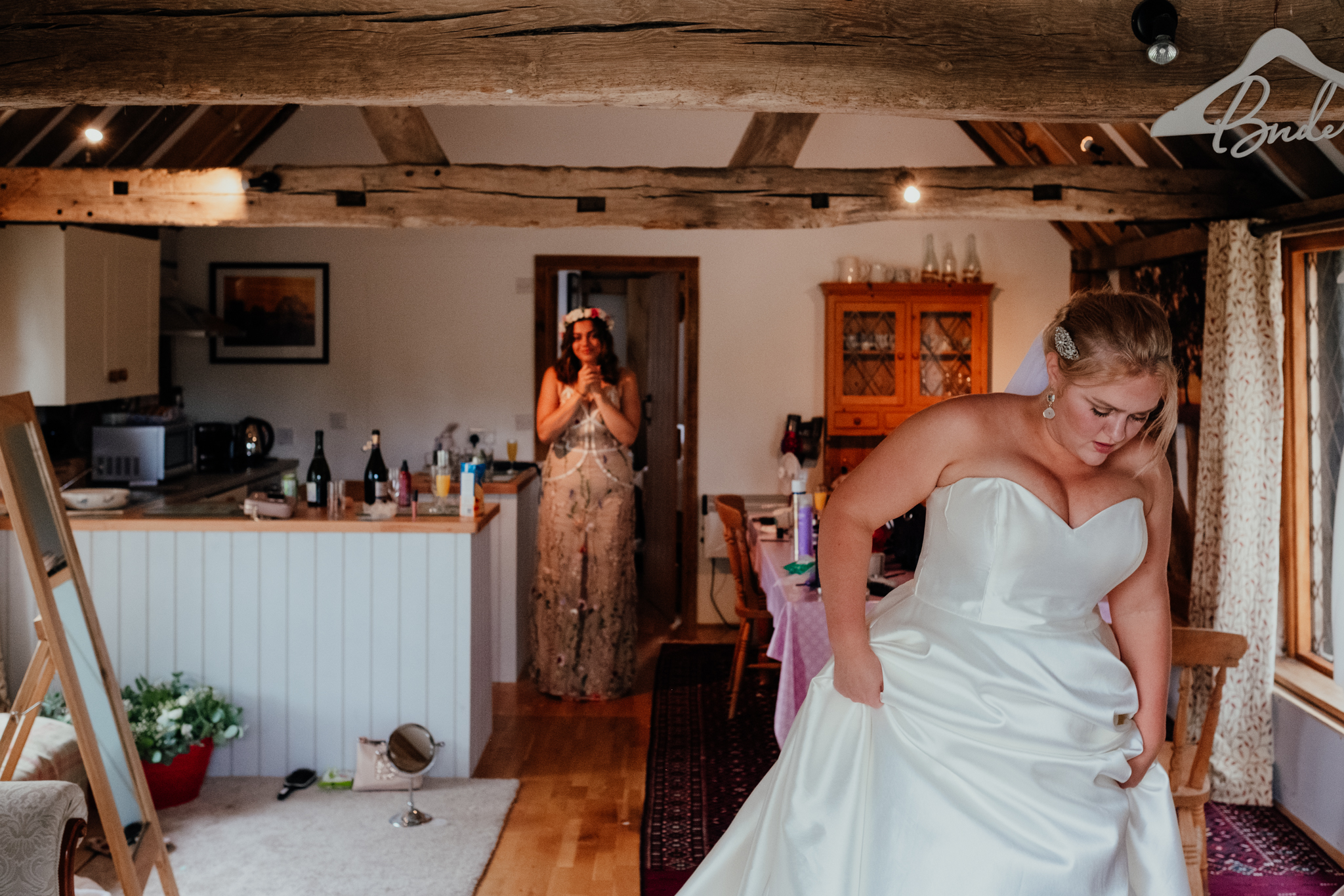 Bride getting ready at Rumbolds Farm while bridesmaid watches