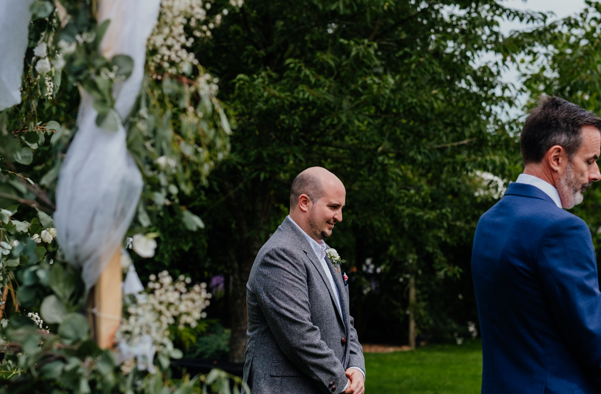 Groom waits for bride at Rumbolds Farm outdoor summer wedding