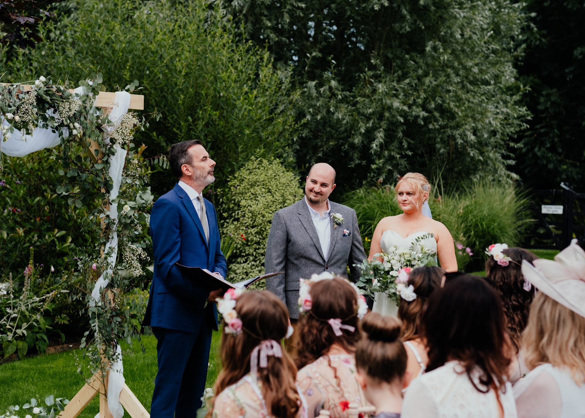 Groom smiles at celebrant during outdoor wedding at Rumbolds Farm