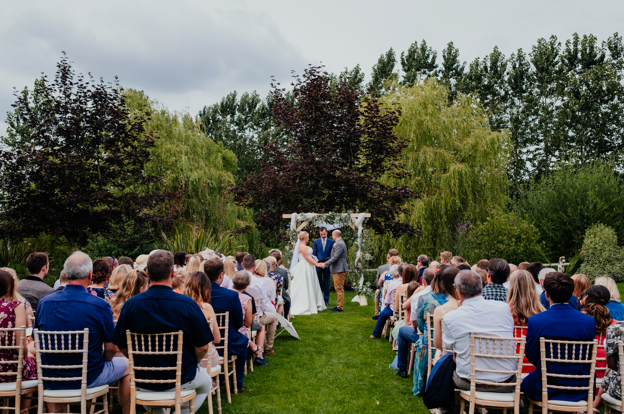 Outdoor wedding ceremony with arch at Rumbolds Farm