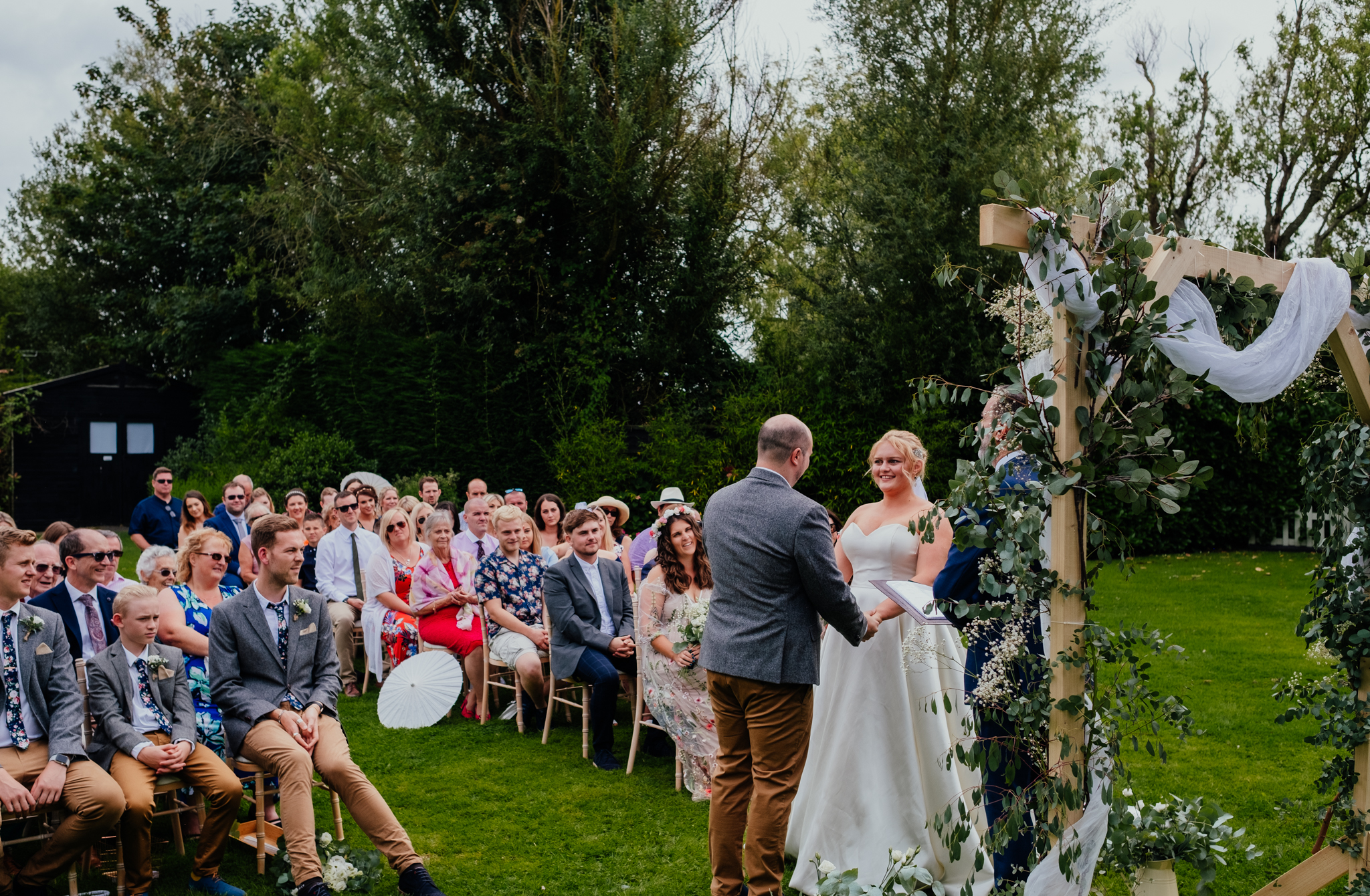 Guests watch as bride and groom exchange vows during outdoor wedding ceremony at Rumbolds Farm