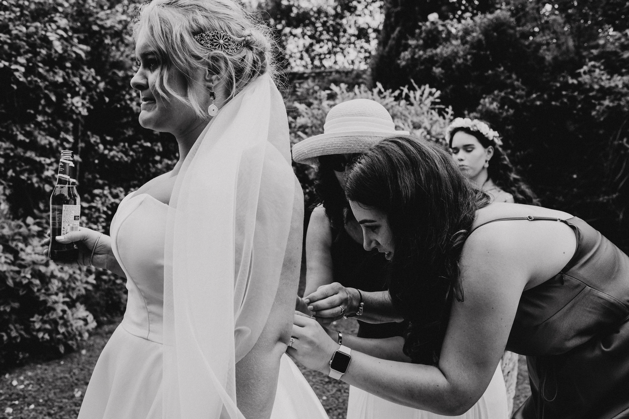 Bride drinks beer as bridesmaids sort out her wedding dress