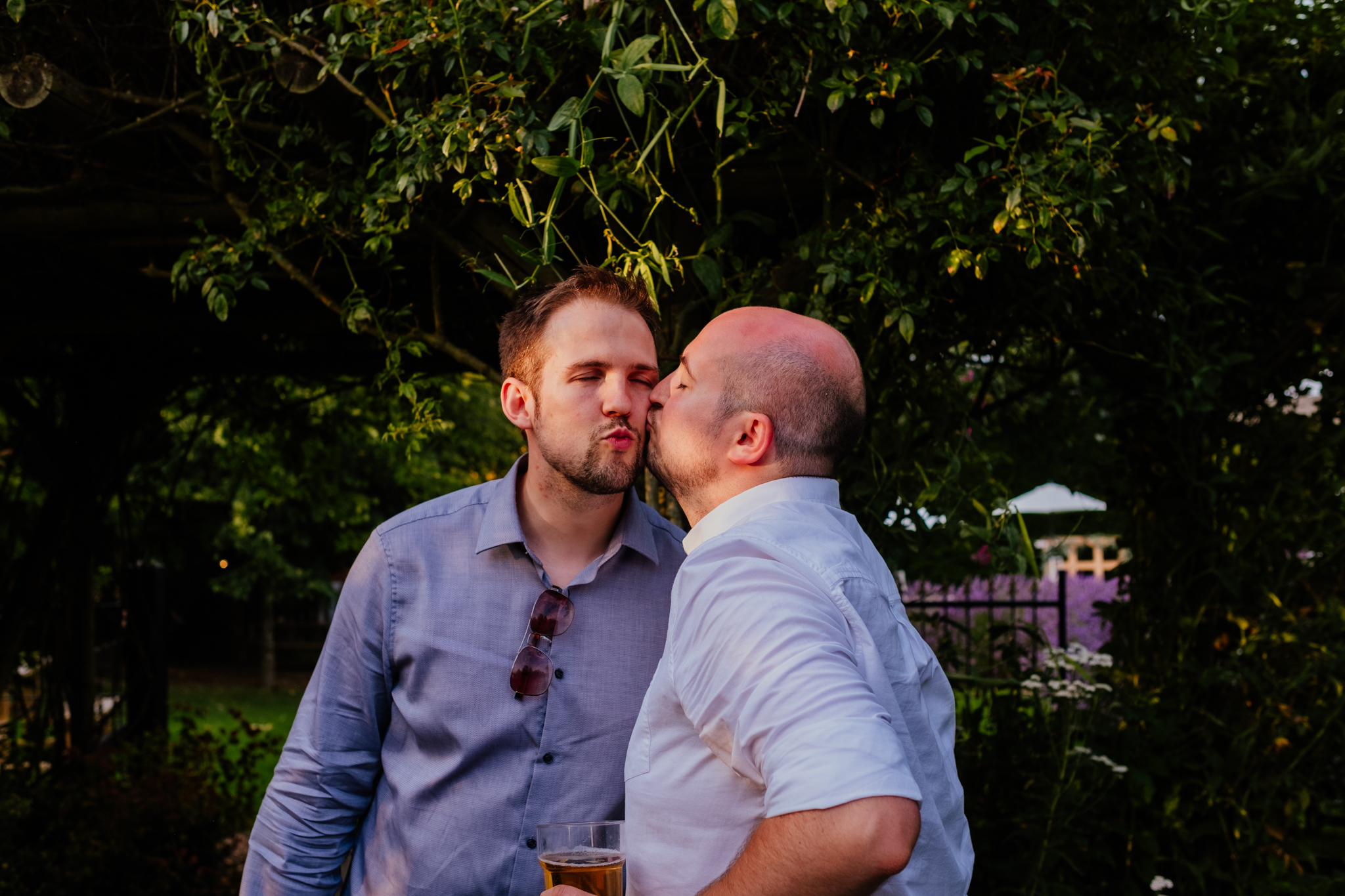 Groom kissing friend on the cheek