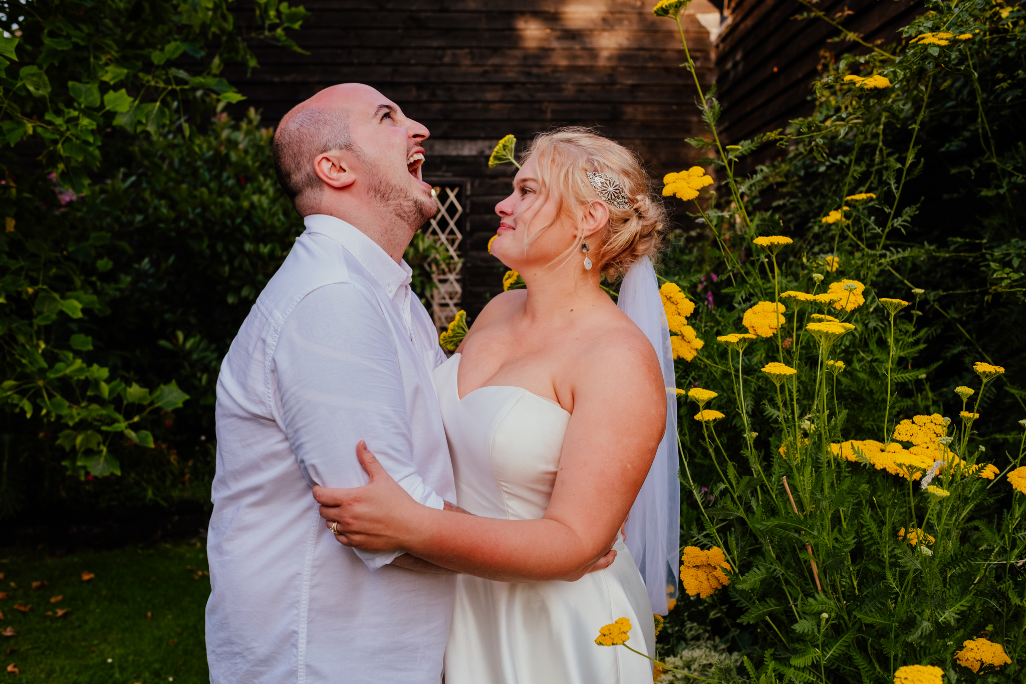 Bride watches groom laugh during golden hour at Rumbolds Farm