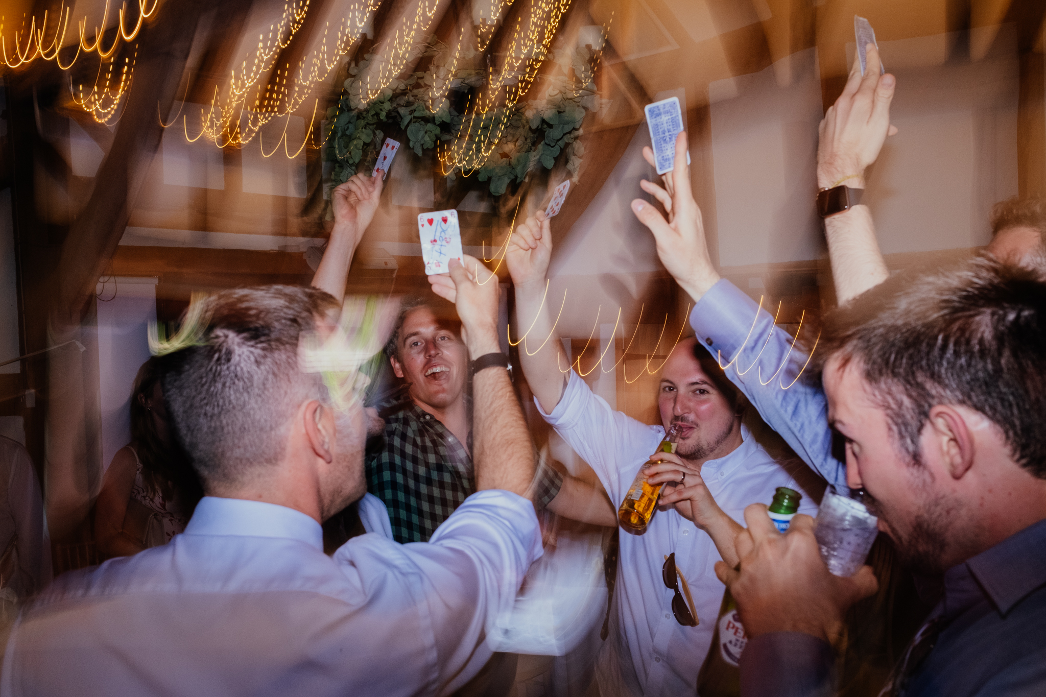 Groom and groomsmen drink beer and hold up cards
