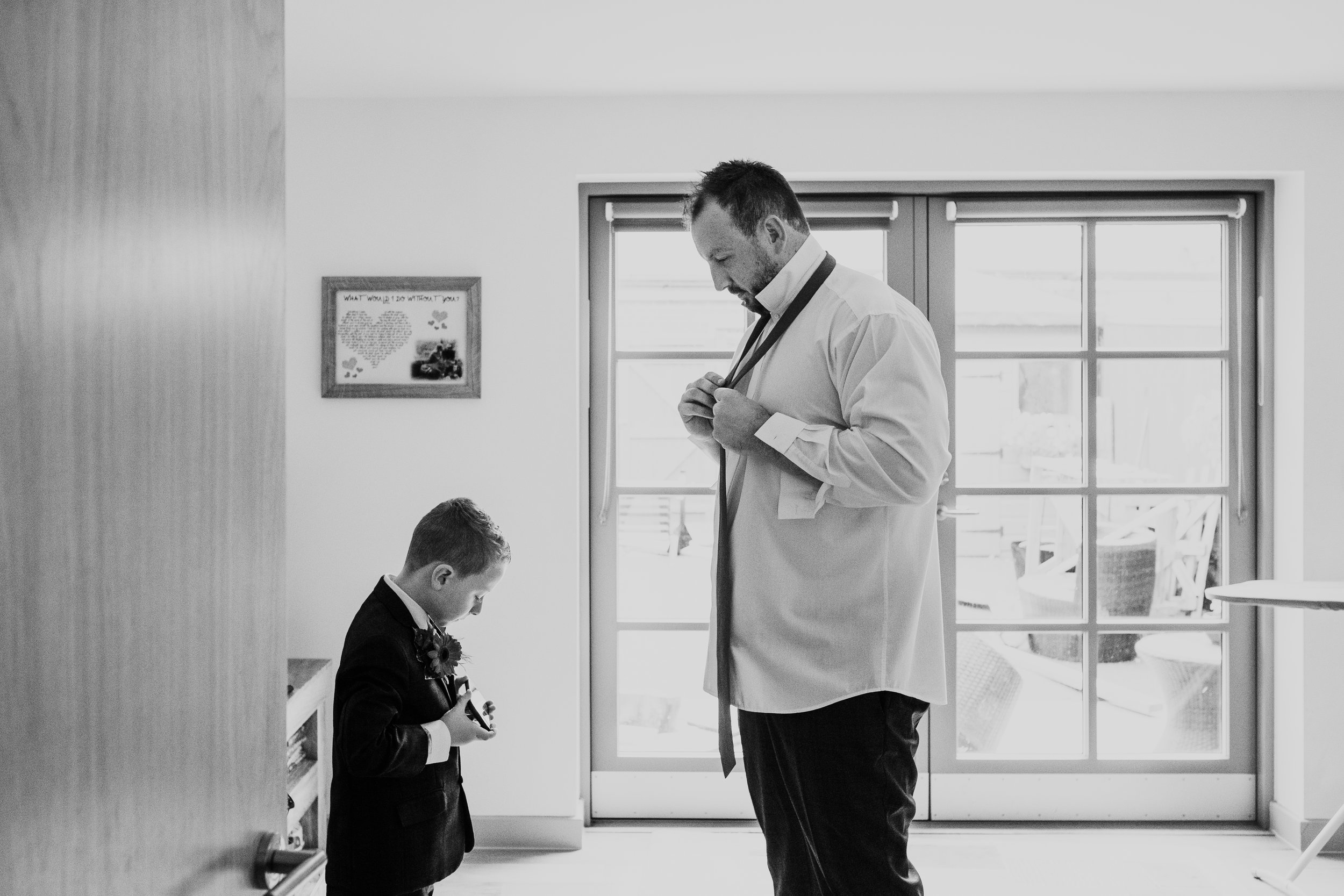 Groom puts on tie with the help of son
