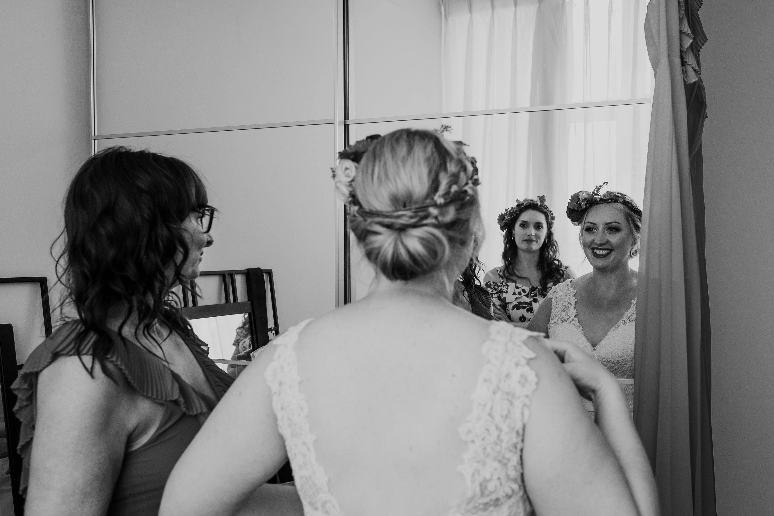 Bride smiles at her sister in reflection of mirror on wedding morning
