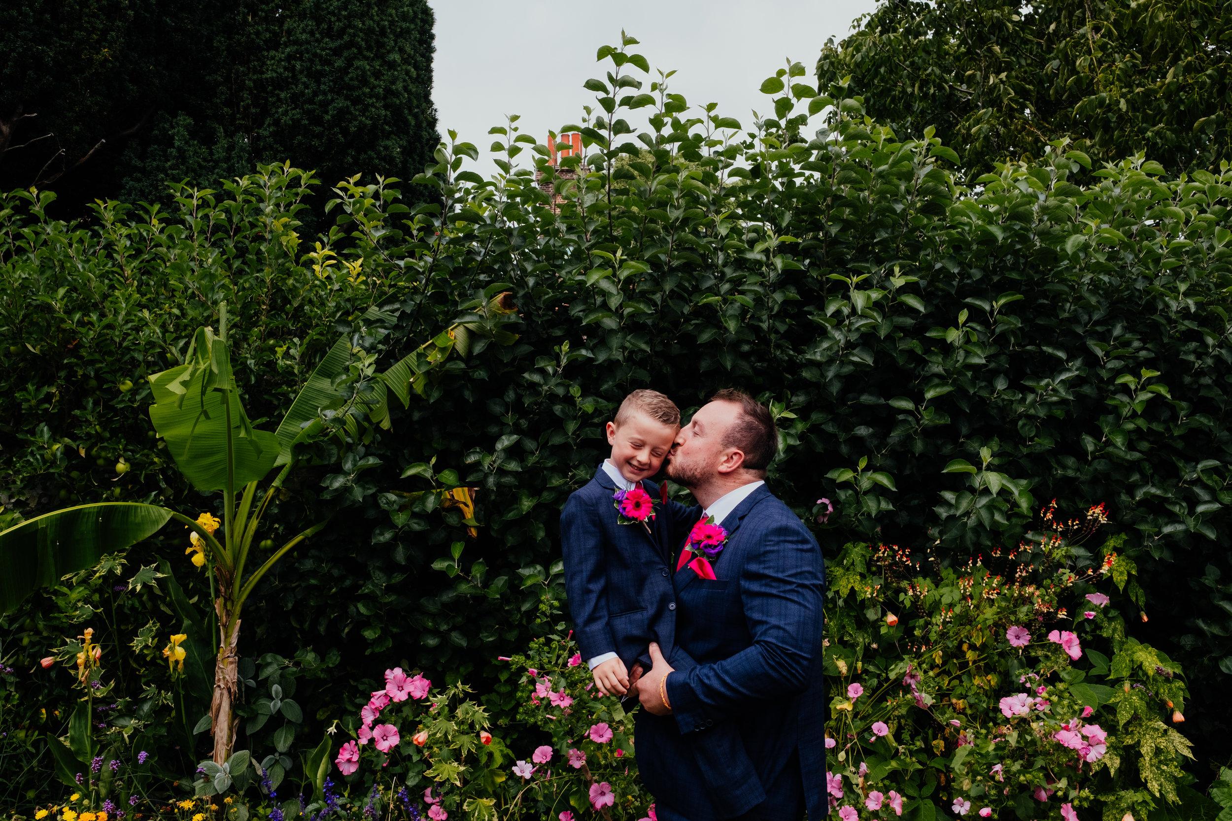 Groom kisses his son on the cheek
