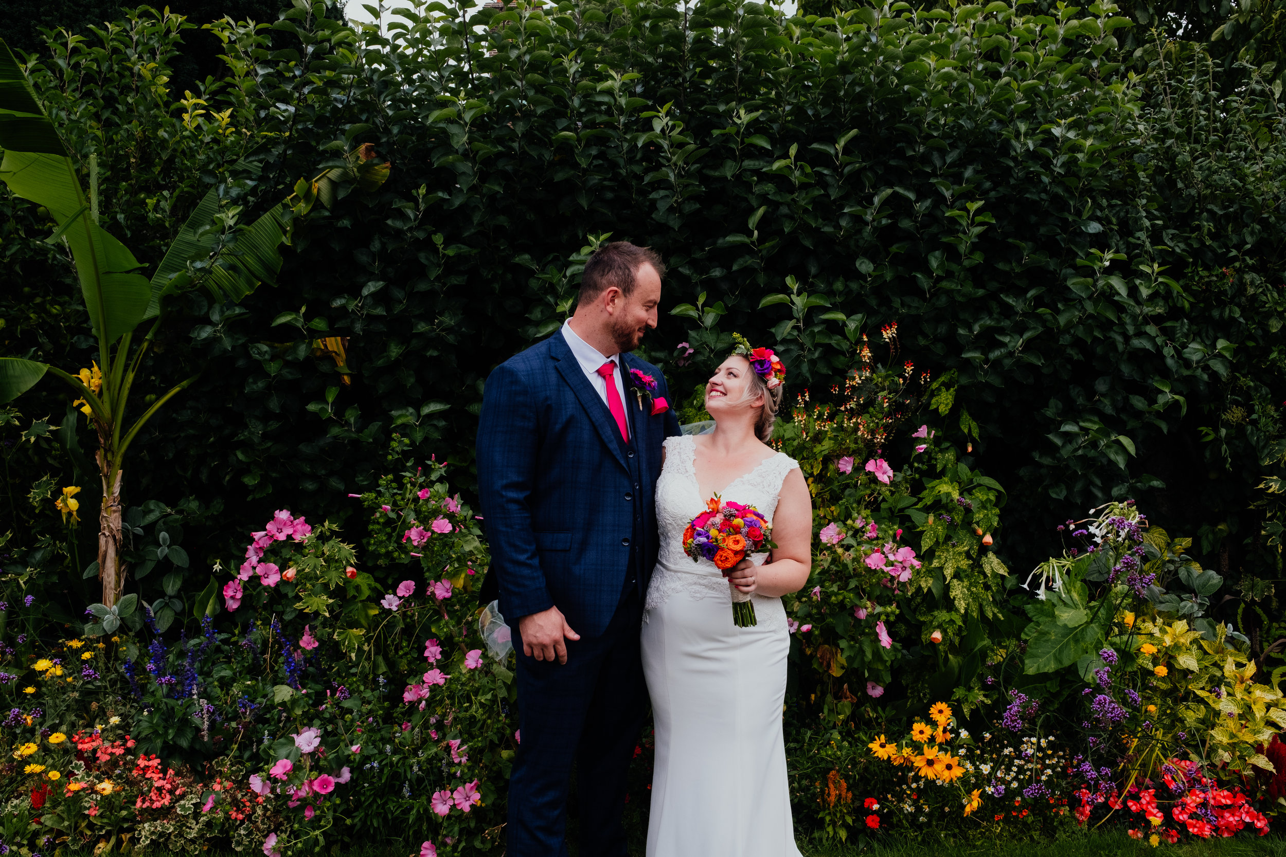 Bride and Groom smiling at each other surrounded by flowers