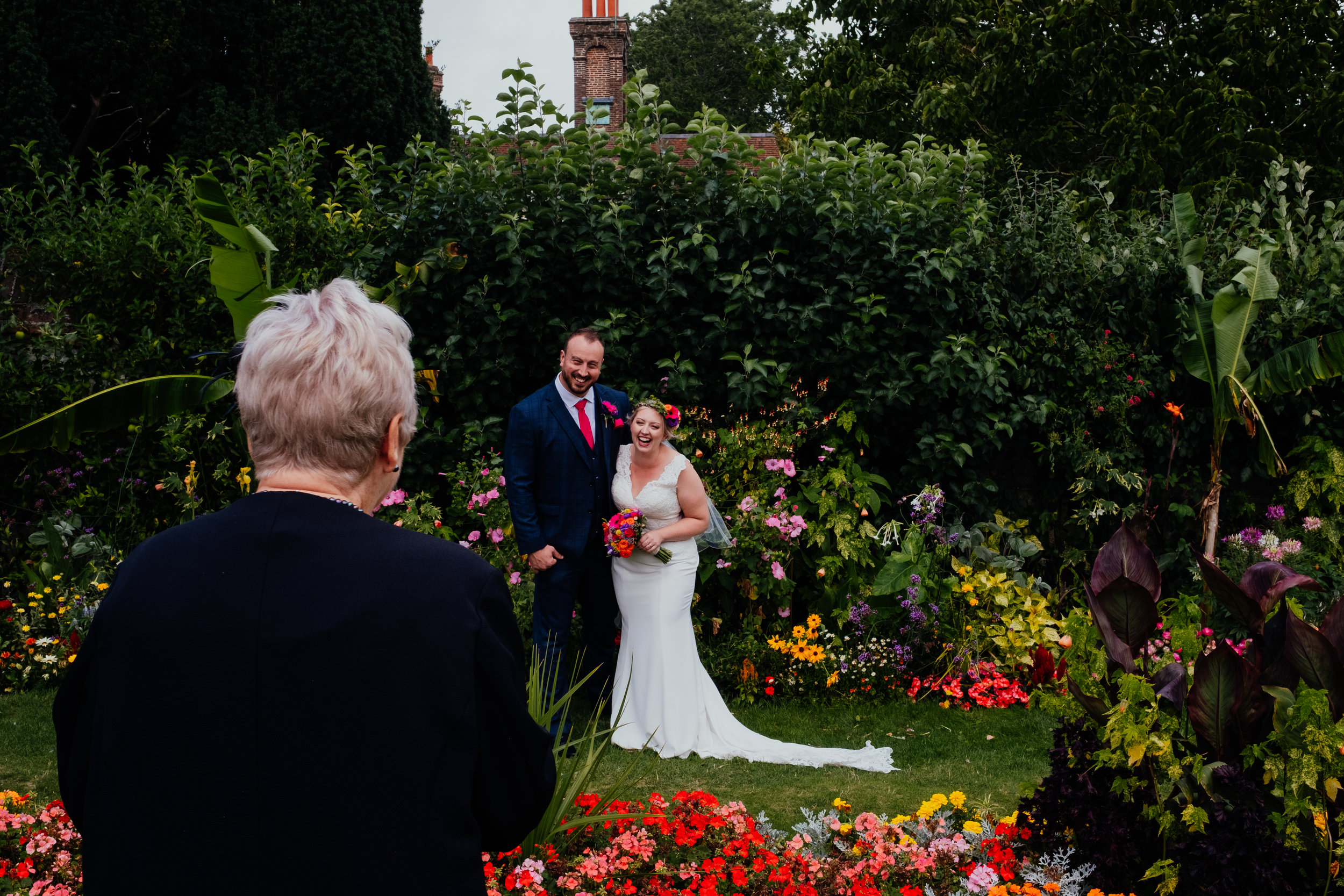 Bride and groom laugh as family take photographs of them