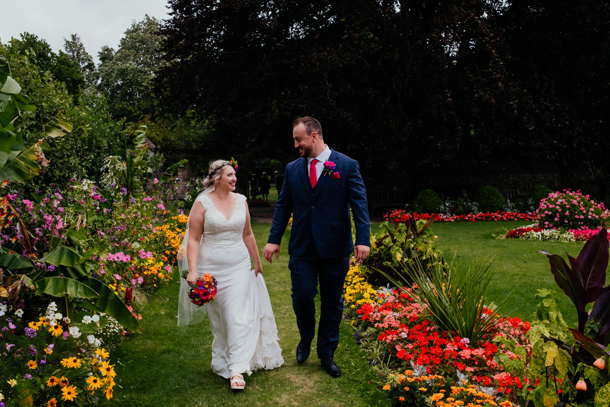 Vegan bride and groom walk through Southover Grange gardens after getting married