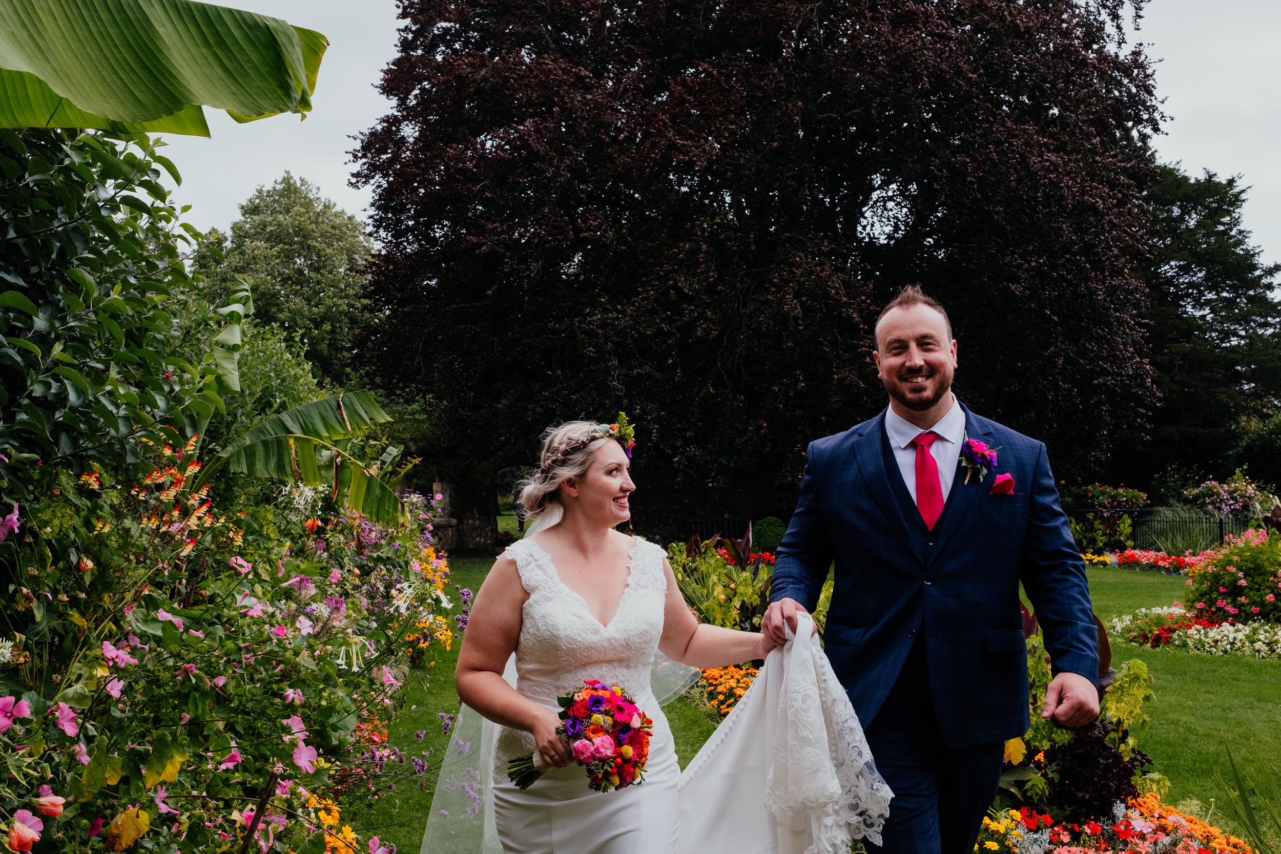 Bride smiling at groom as they walk through flower garden