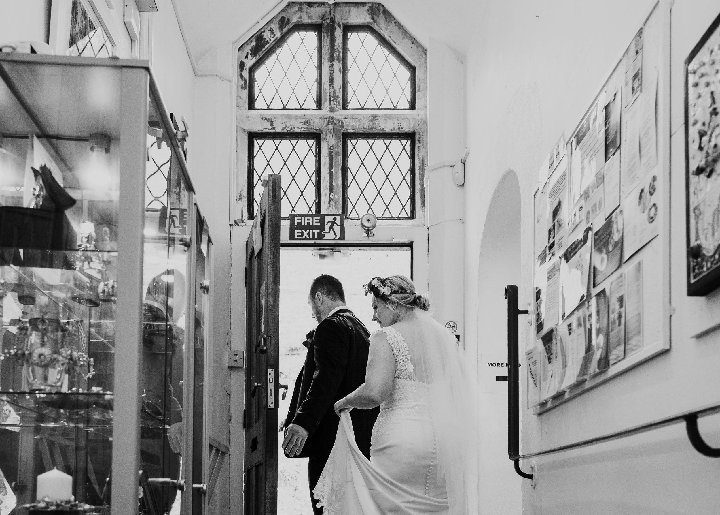 Bride and groom walking through museum