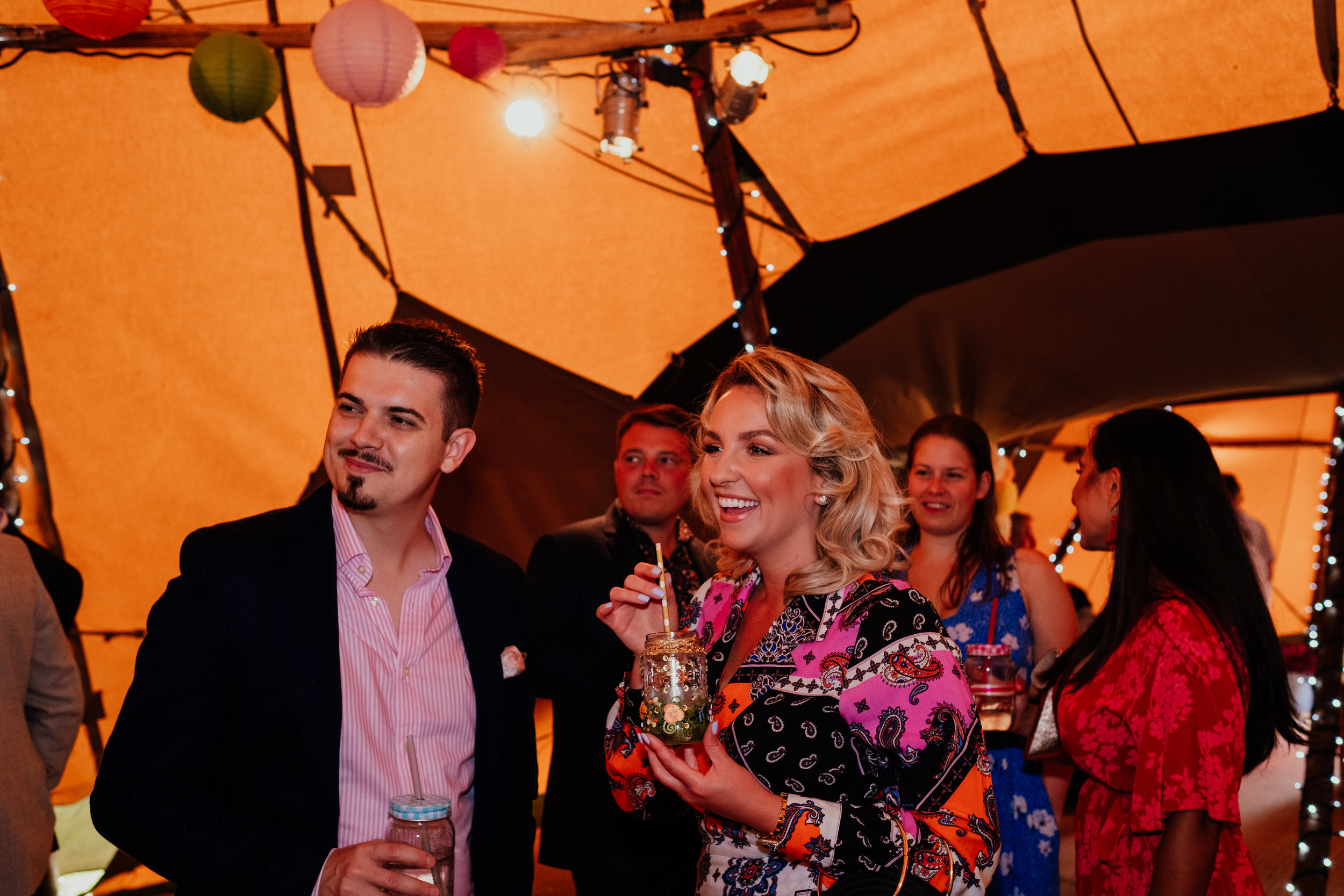 Guests drinking wine at Four Oaks Farm tipi wedding