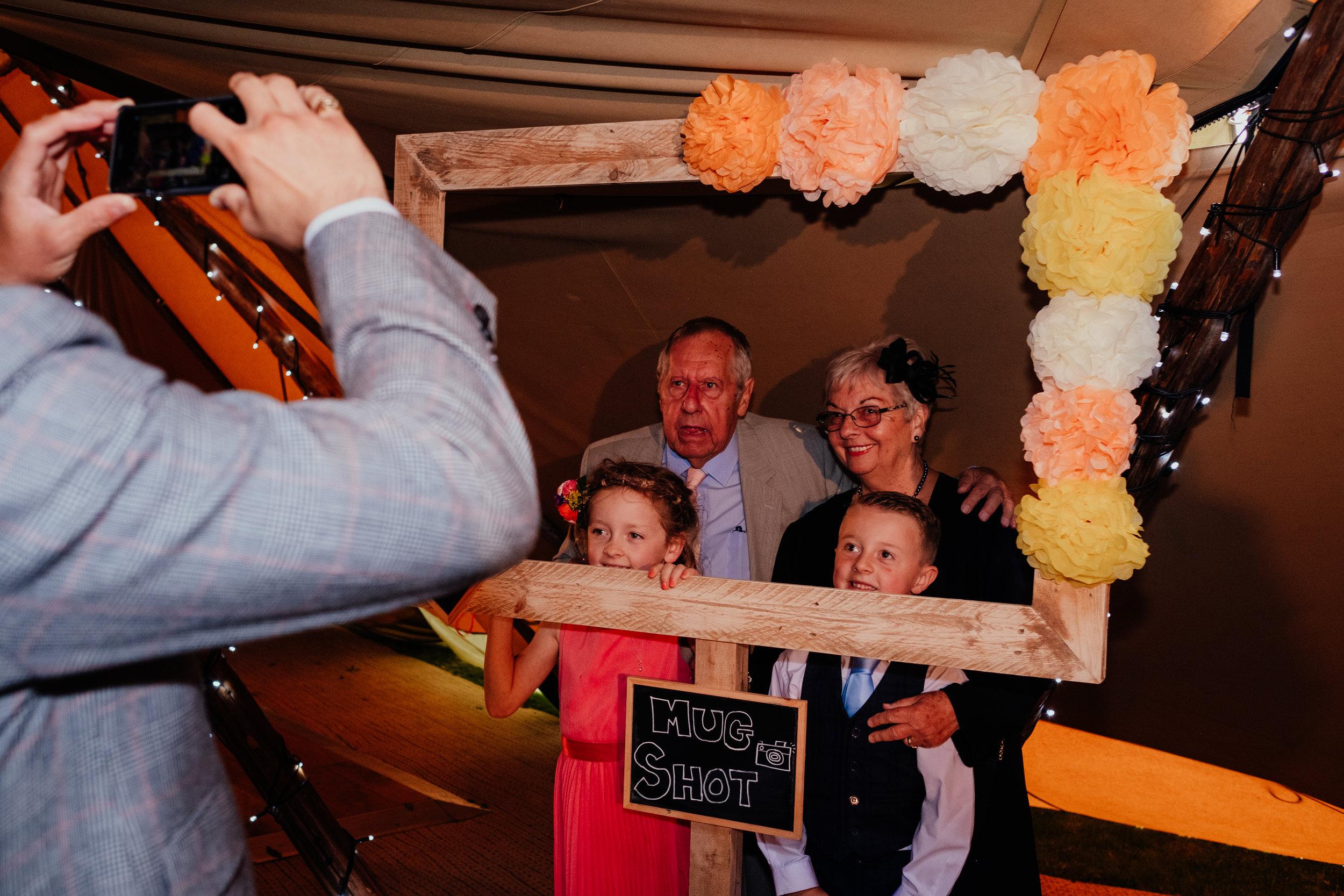 Family taking photos at tipi wedding