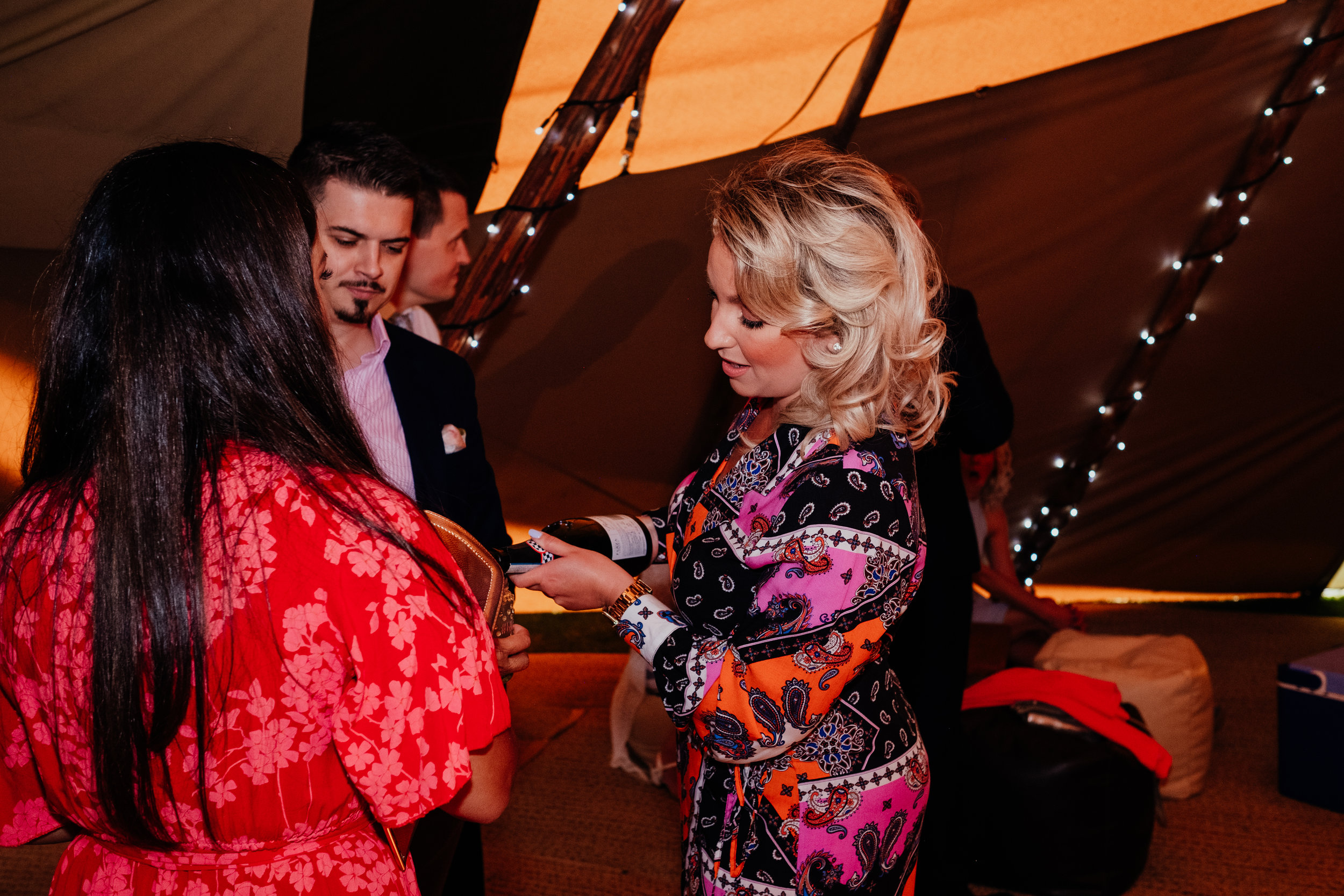 wedding guests pouring wine at tipi wedding
