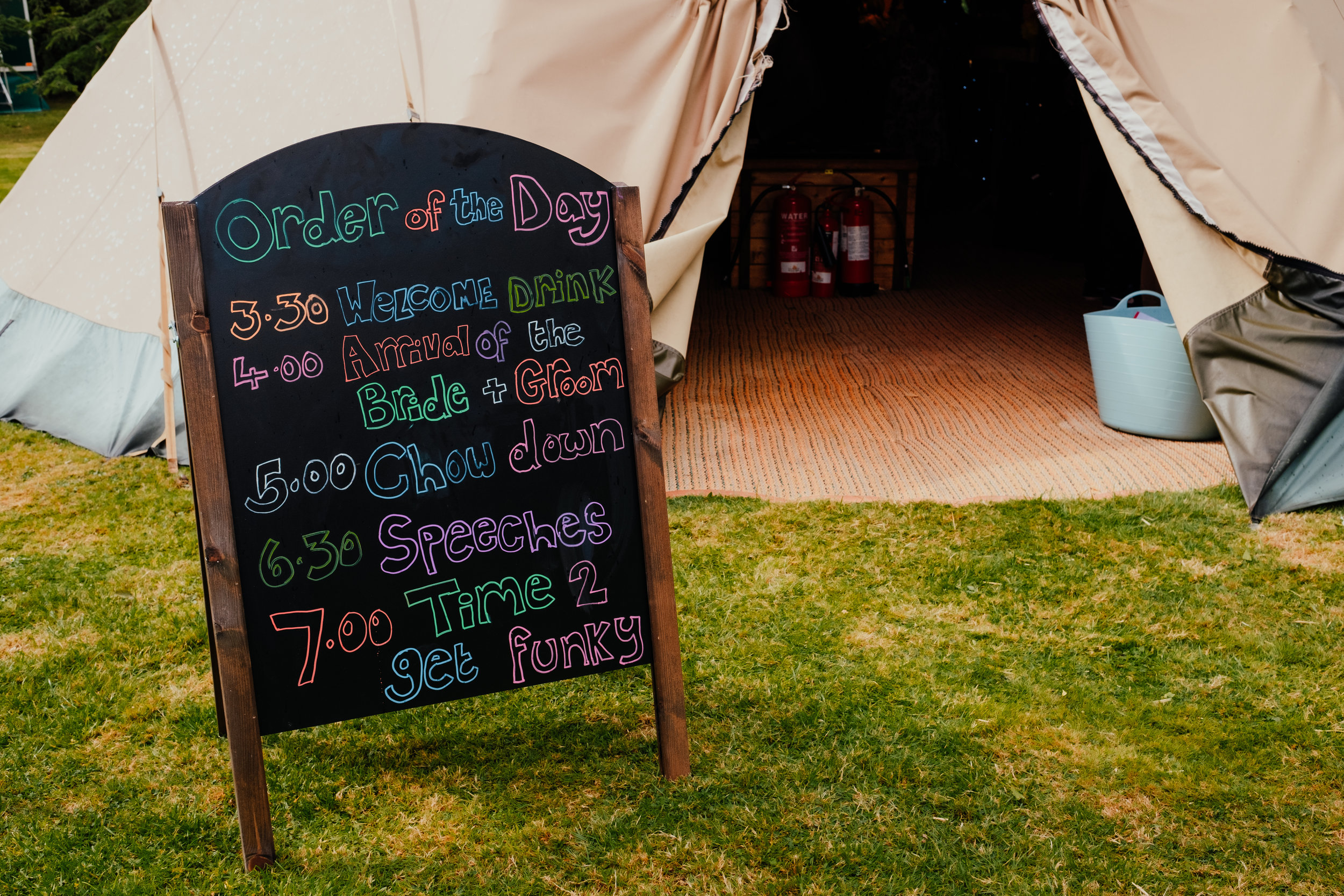 Order of the day on chalk board outside wedding tipi