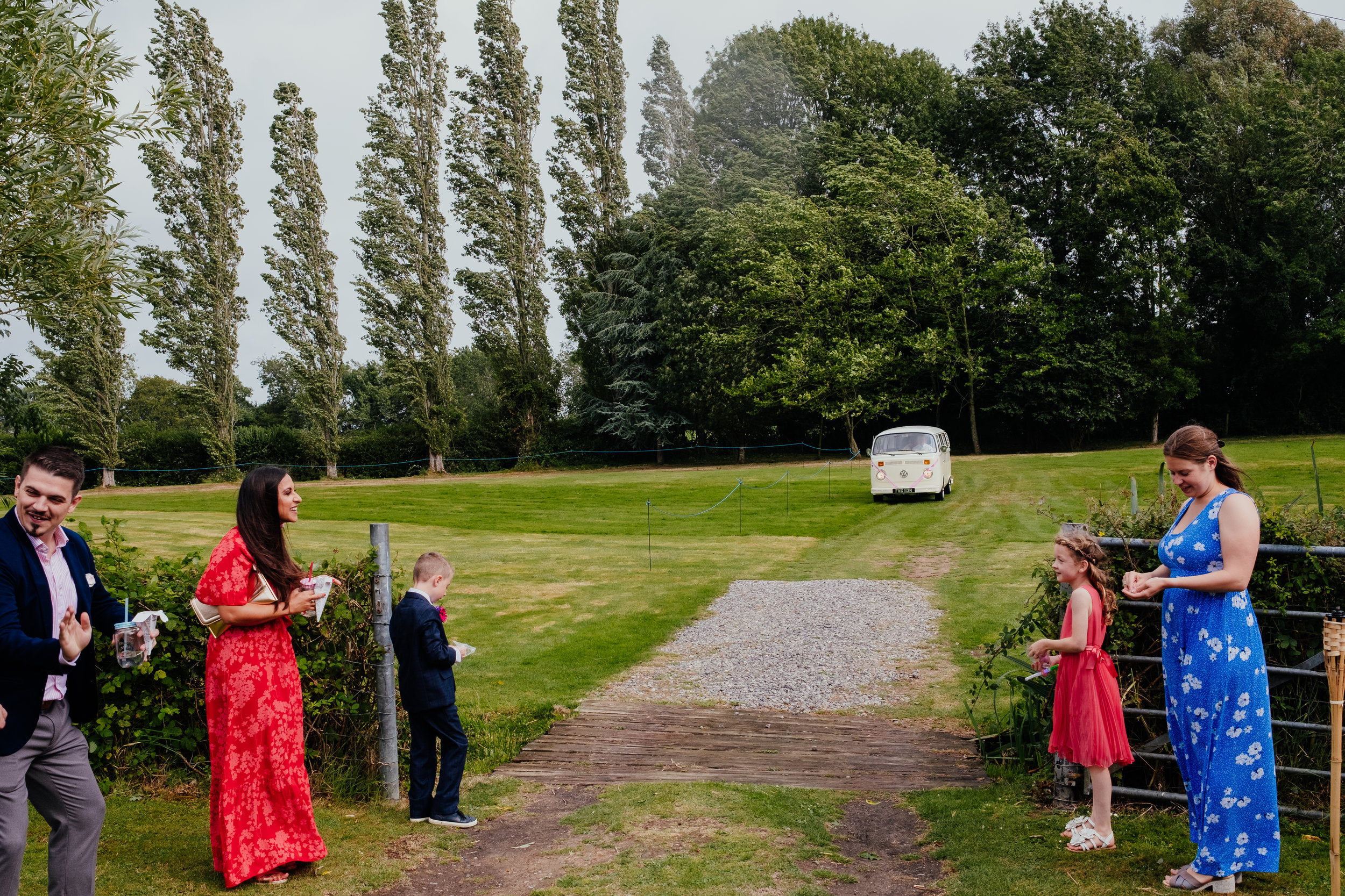 Bride and groom arriving at Four Oaks Farm tipi wedding in cream vw camper van
