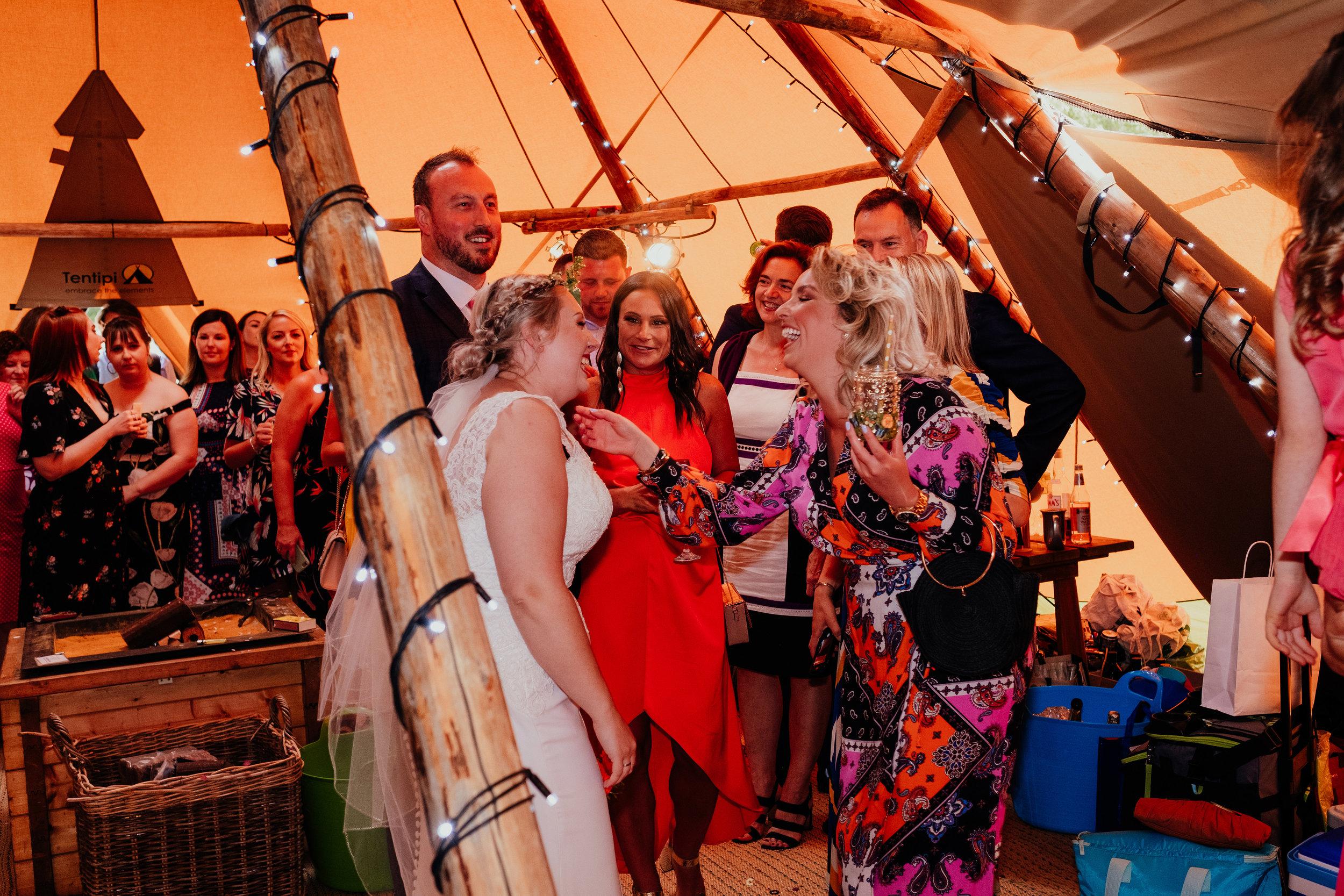 Wedding guests greet bride and groom at vegan tipi wedding