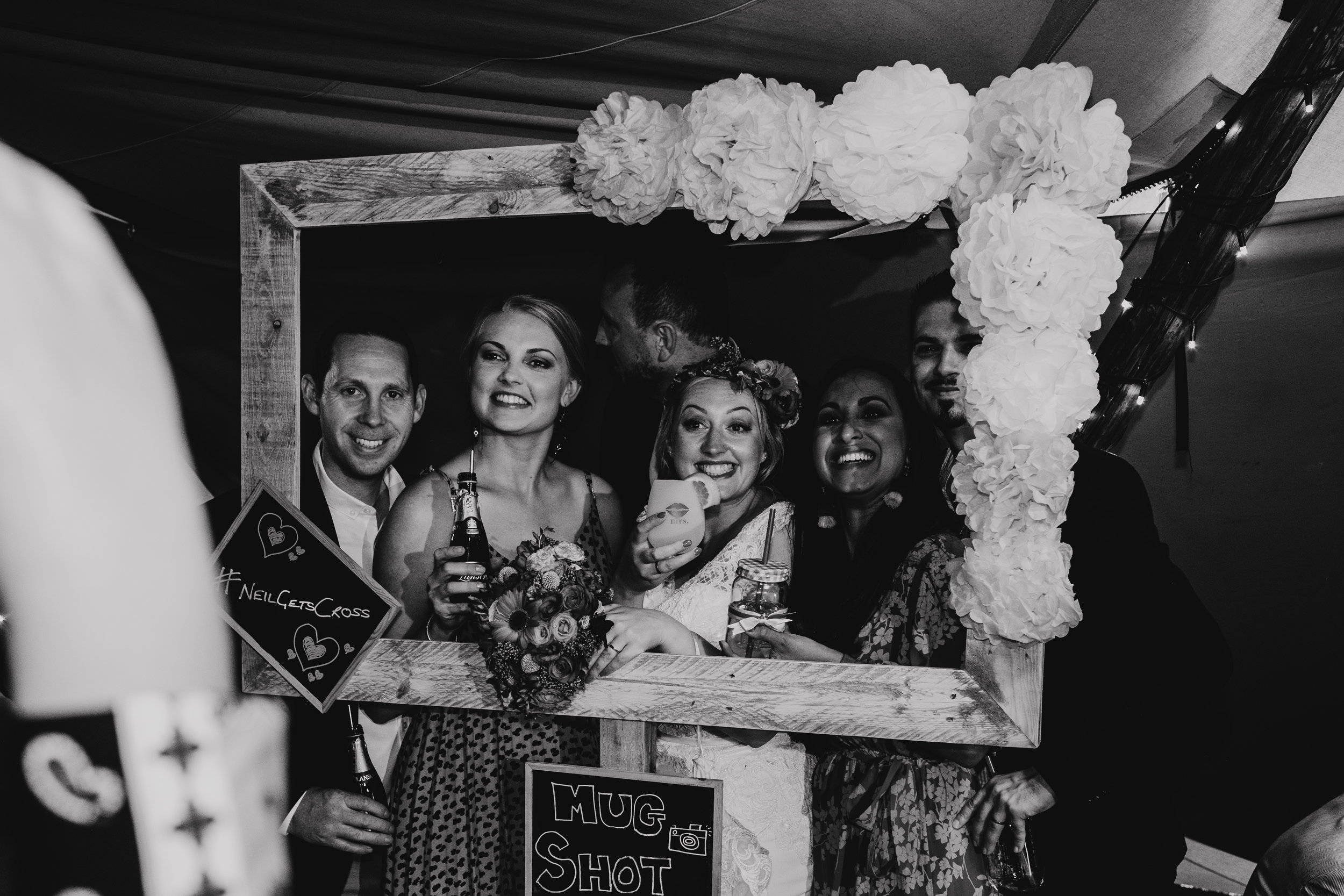 Bride and friends posing for photograph with large photo frame