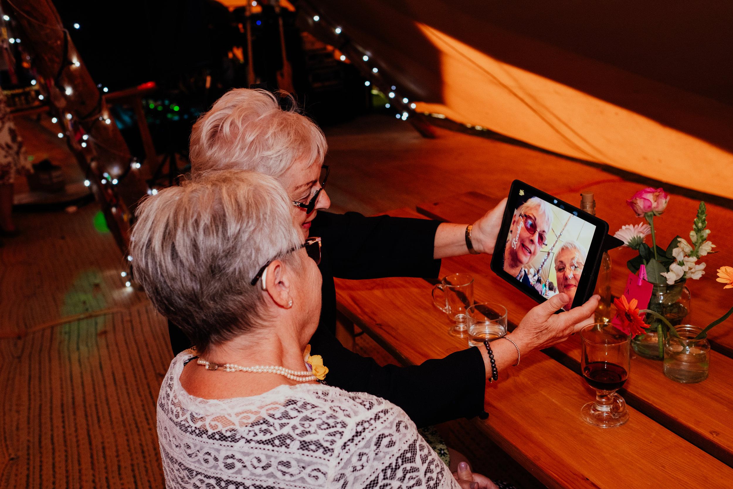 Wedding guests recording congratulations message on iPad