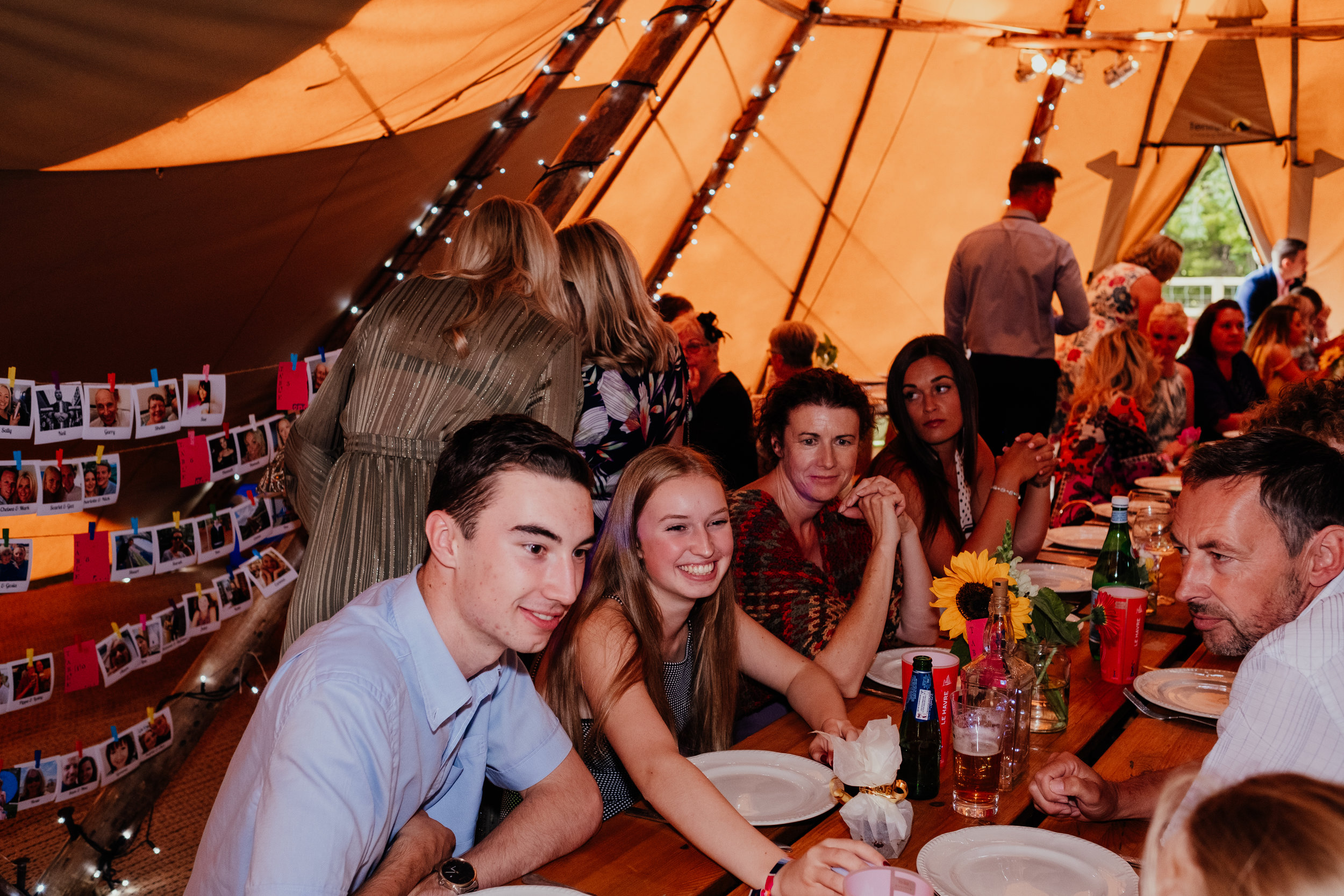 Wedding guests sitting down to eat in wedding tipi