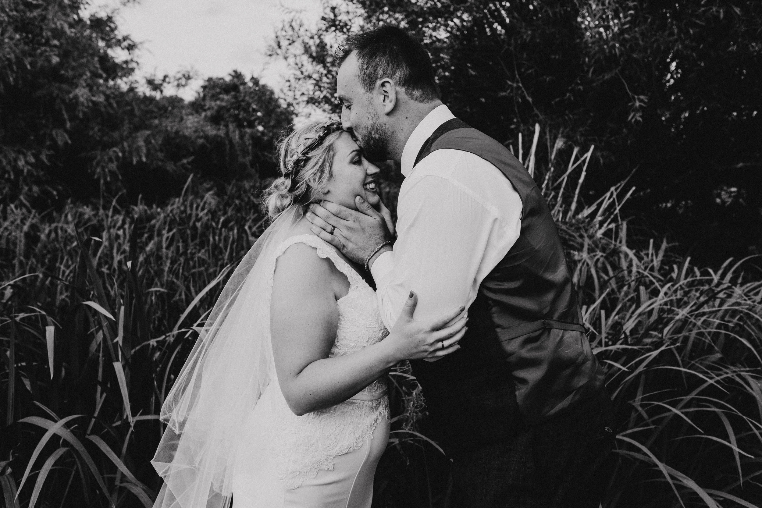 Groom kisses vegan bride on forehead