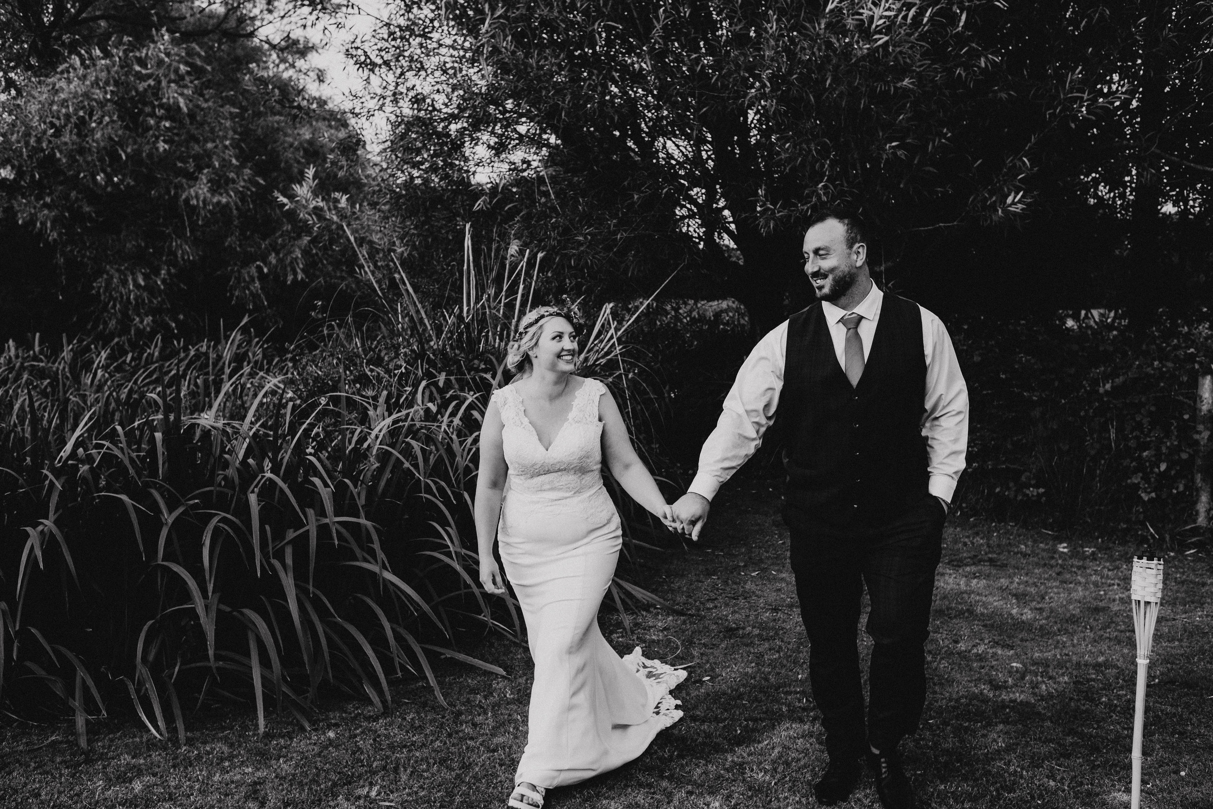 Vegan bride and groom walk through the fields at Four Oaks Farm tipi wedding