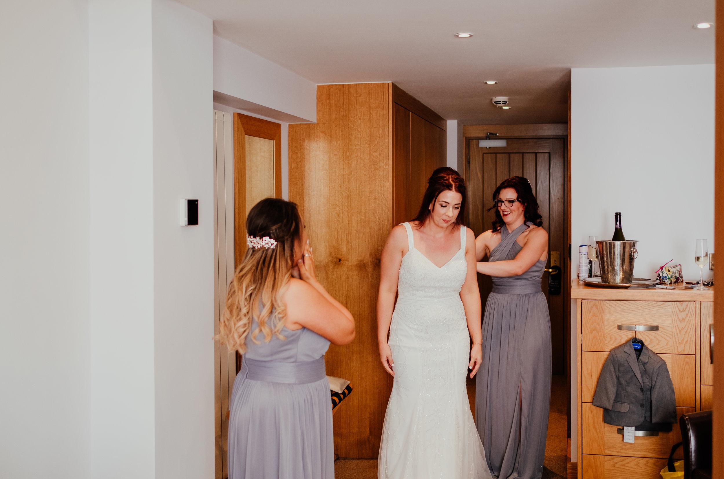Bride puts on wedding dress on morning of Tewin Bury Farm wedding