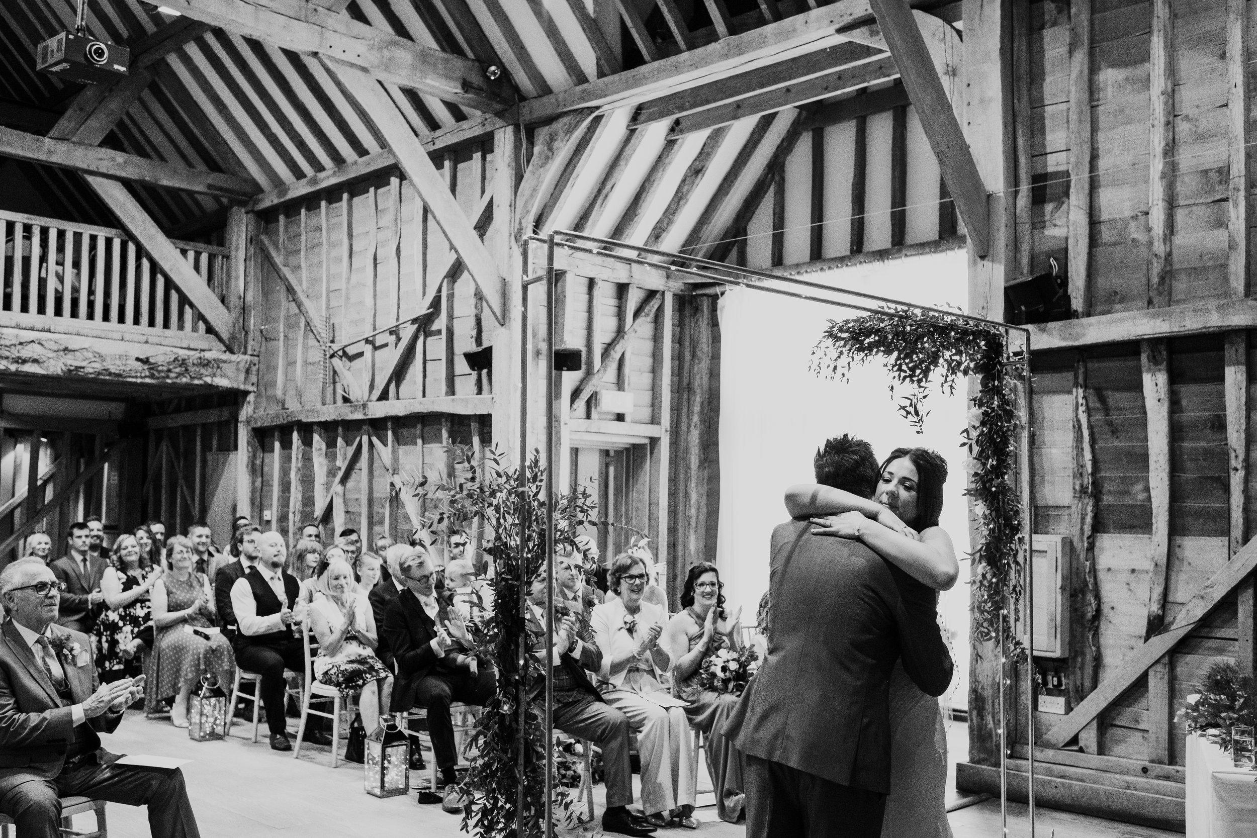 Bride hugs groom during Tewin Bury Farm wedding ceremony