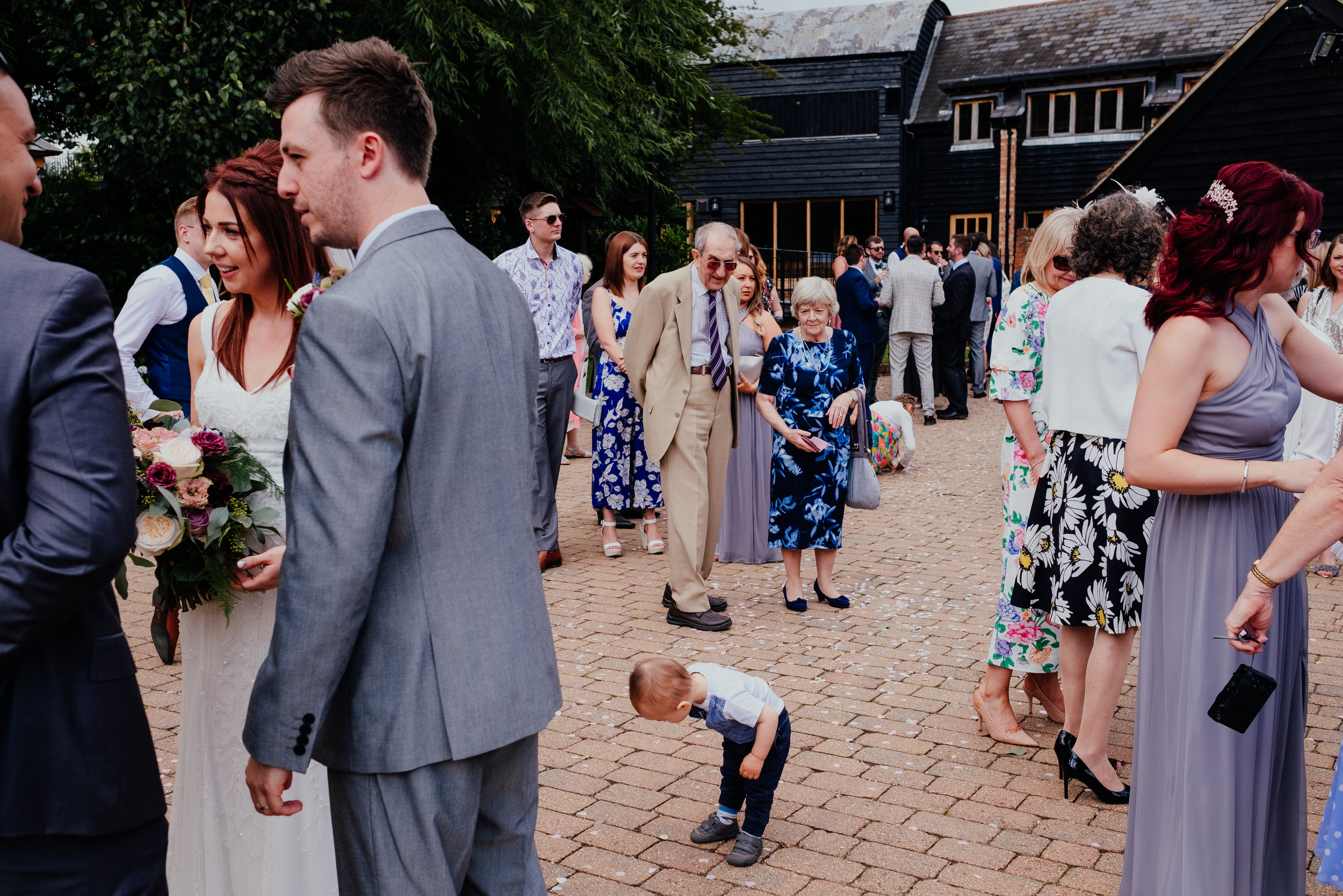 Wedding guests watch small child at Tewin Bury Farm wedding